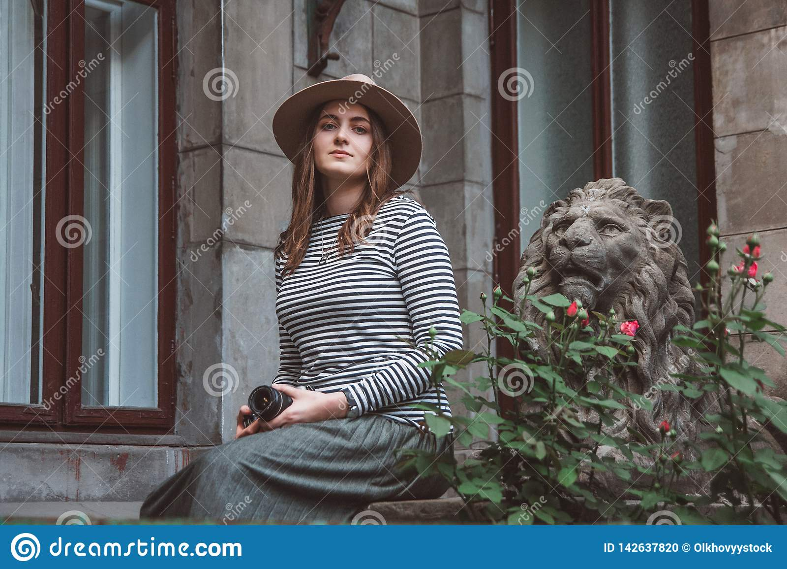 Piękna kobieta w pasiastym kapeluszu i koszula Trzyma kamerę blisko statuy lew przeciw tłu stary