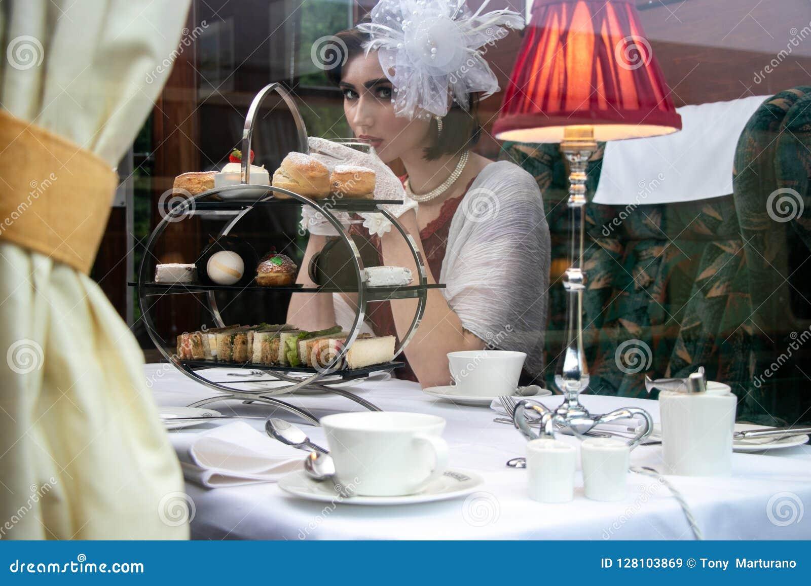 Piękna kobieta w rocznik odzieży cieszy się popołudniowej herbaty w taborowym frachcie