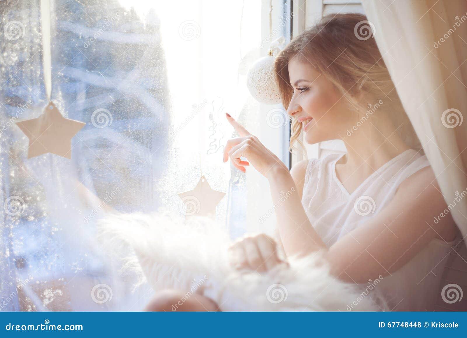 Piękna kobieta z świeżym dziennym makeup i romantyczną falistą fryzurą siedzi przy windowsill, rysuje na szkle
