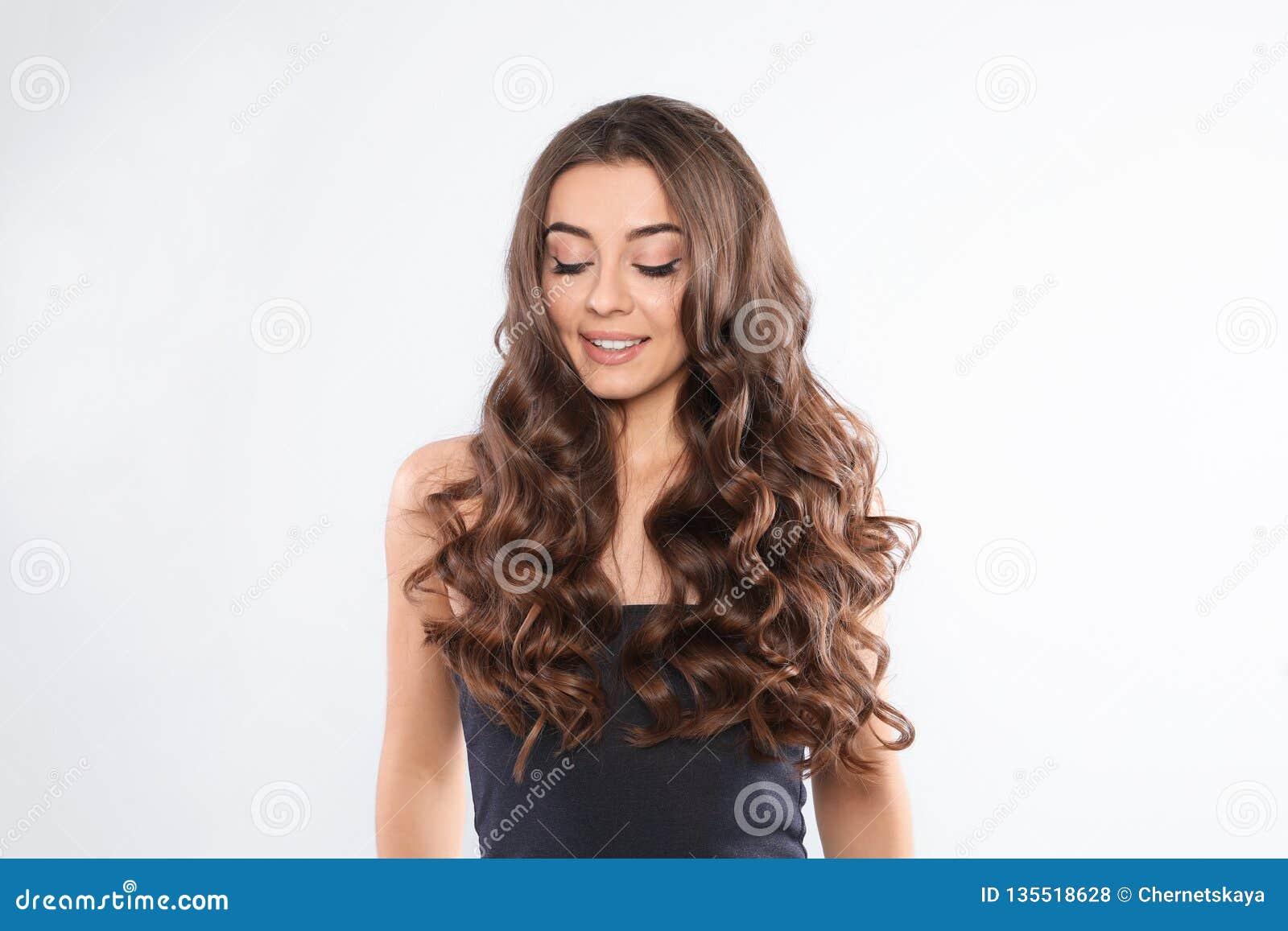 Piękna kobieta z błyszczącym falistym włosy na bielu