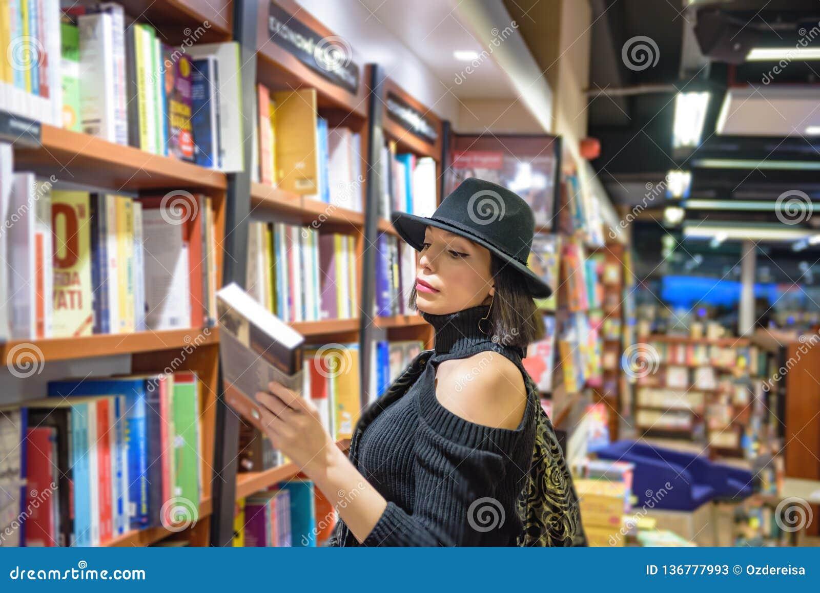Piękna kobieta z czarnym kapeluszem jest w bookstore