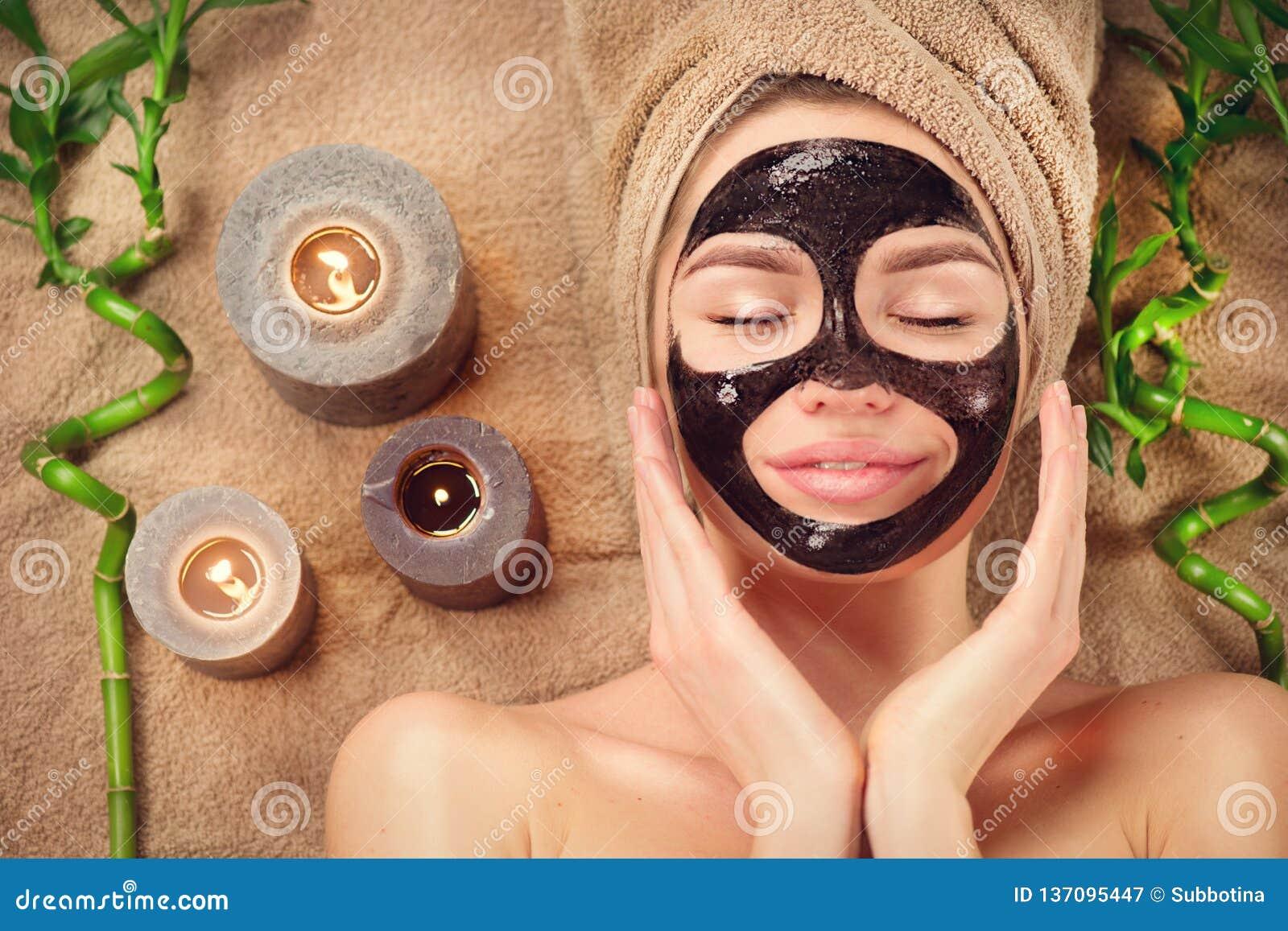 Piękna kobieta z czerni purifying czerni maską na jej twarzy Piękno wzorcowa dziewczyna z czarnym twarzowym łupy maski lying on t
