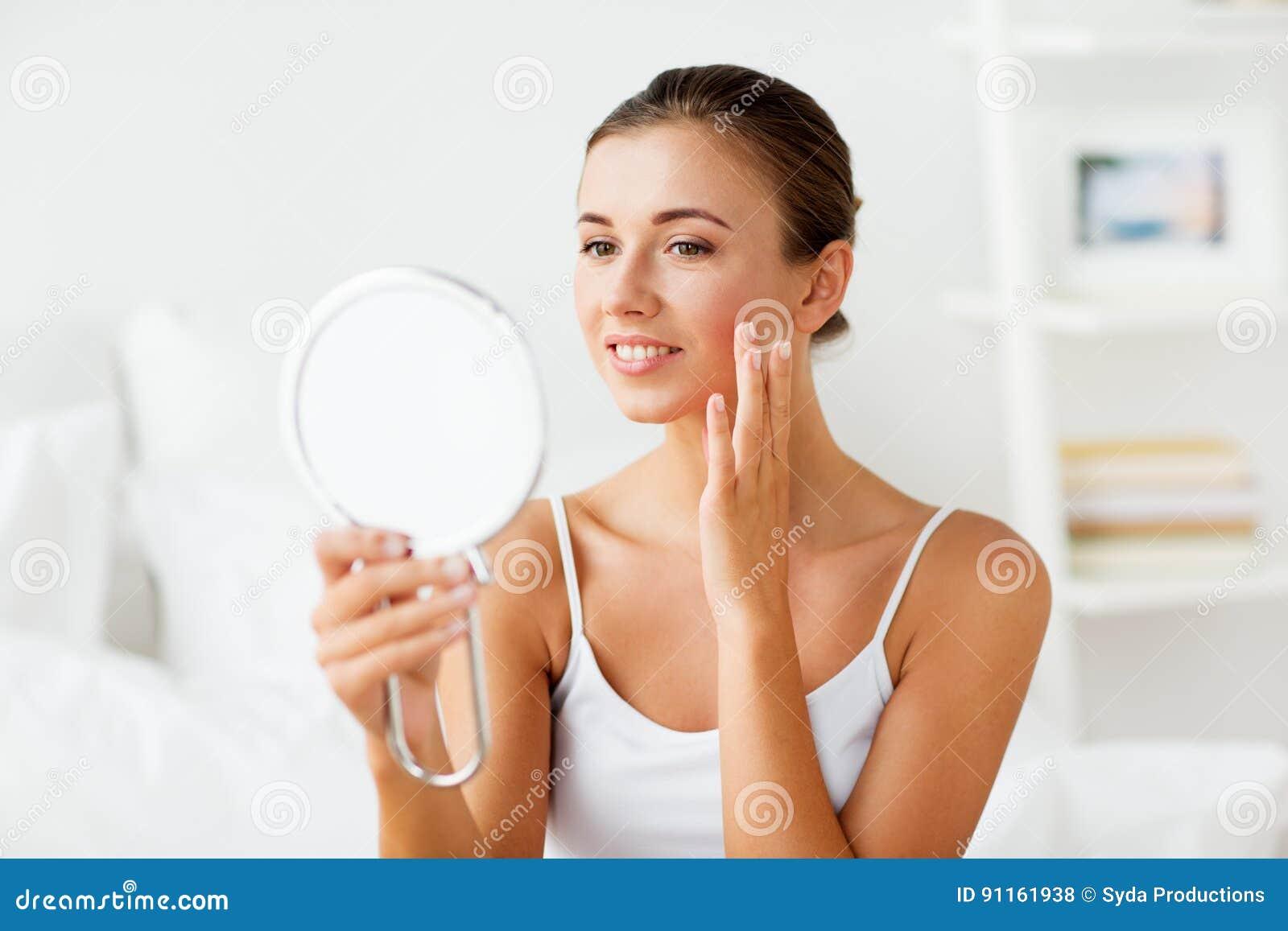 Piękna kobieta z lustrzanym macaniem jej twarzy skóra