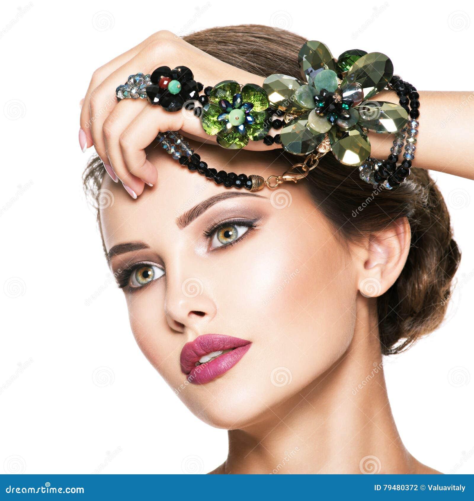 Piękna kobieta z modną zieloną biżuterią