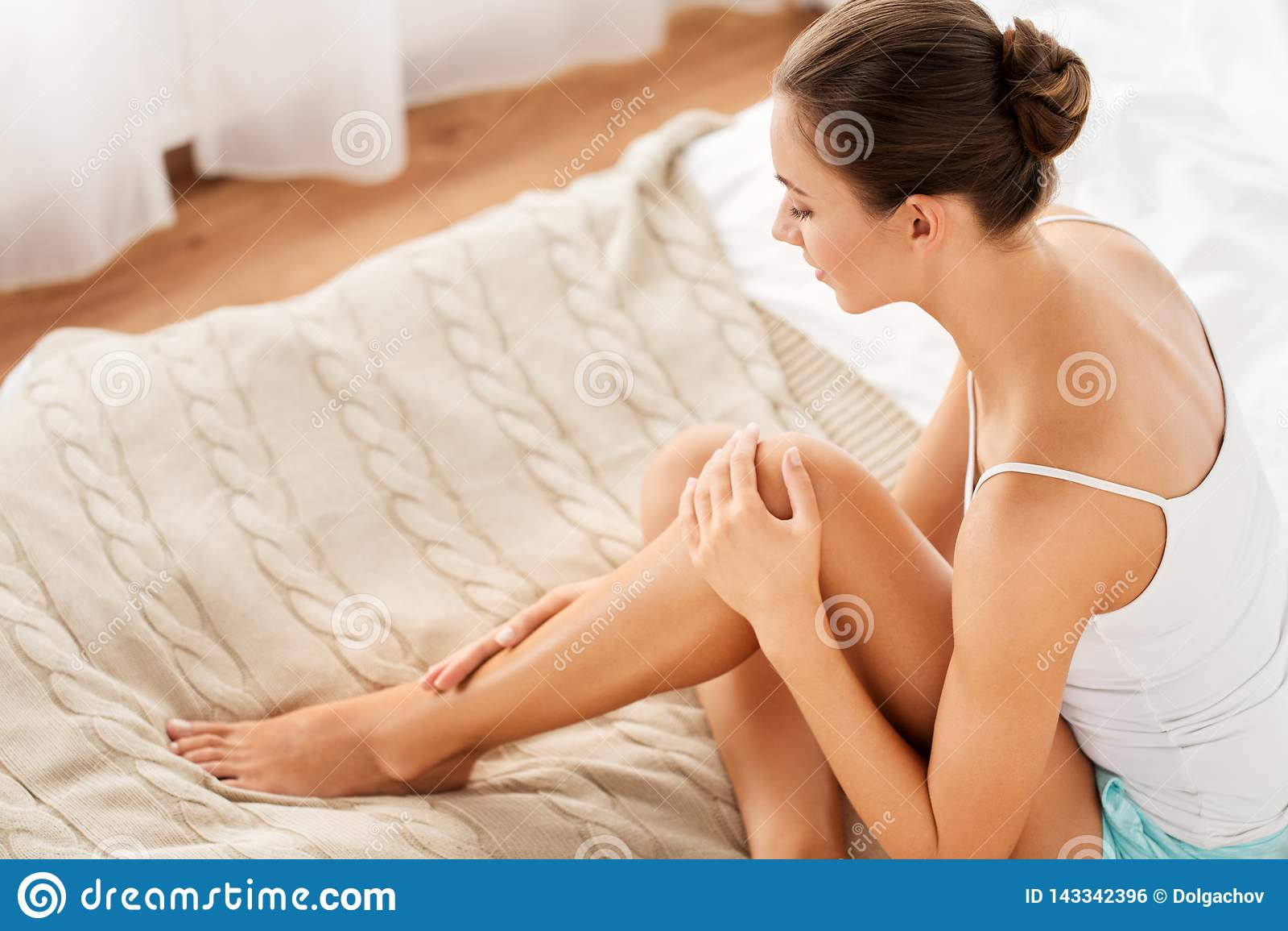 Piękna kobieta z nagimi nogami na łóżku w domu