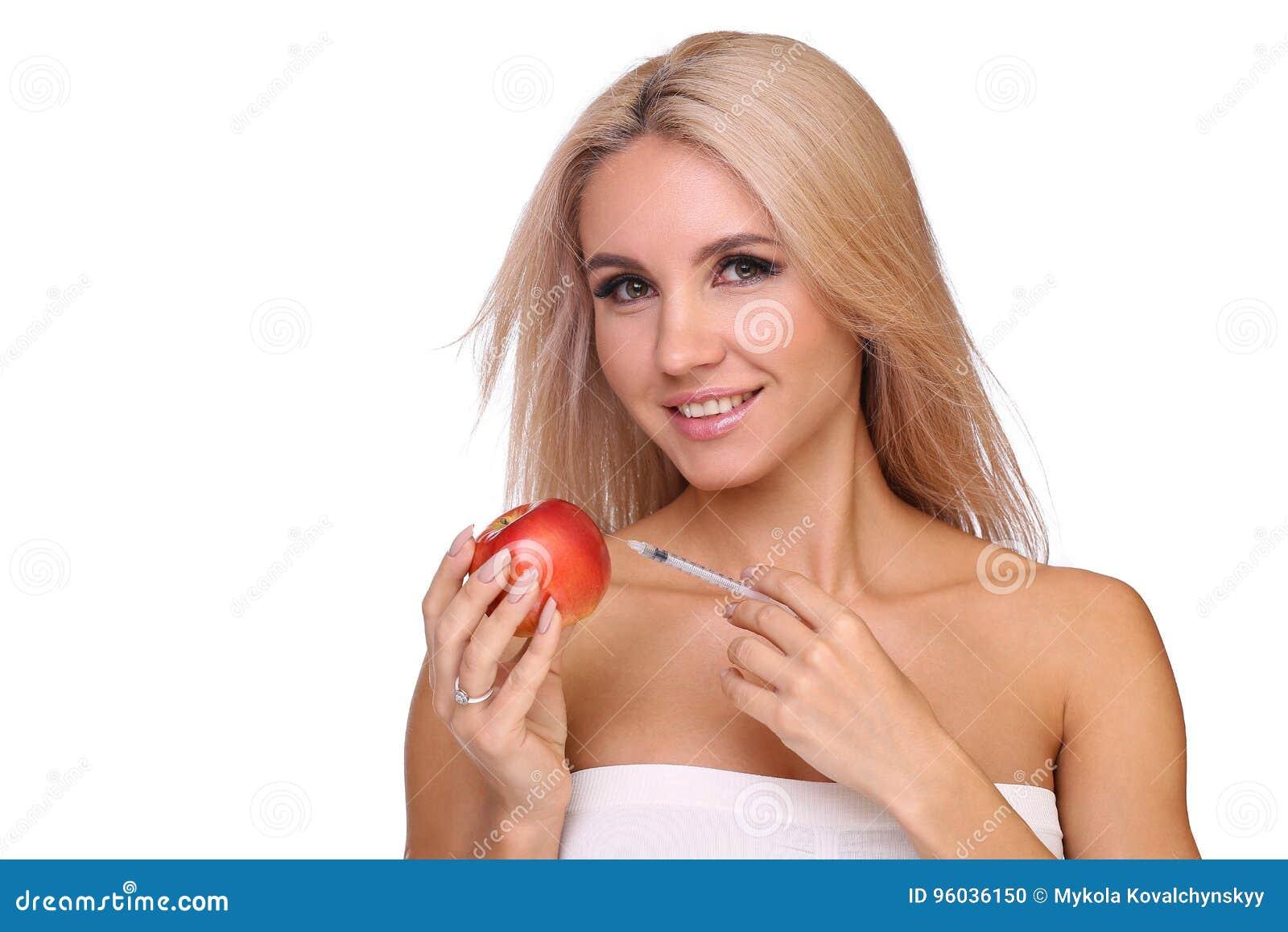 Piękna kobieta z strzykawką czerwona krowiankowa dawka wstrzykuje na jabłku