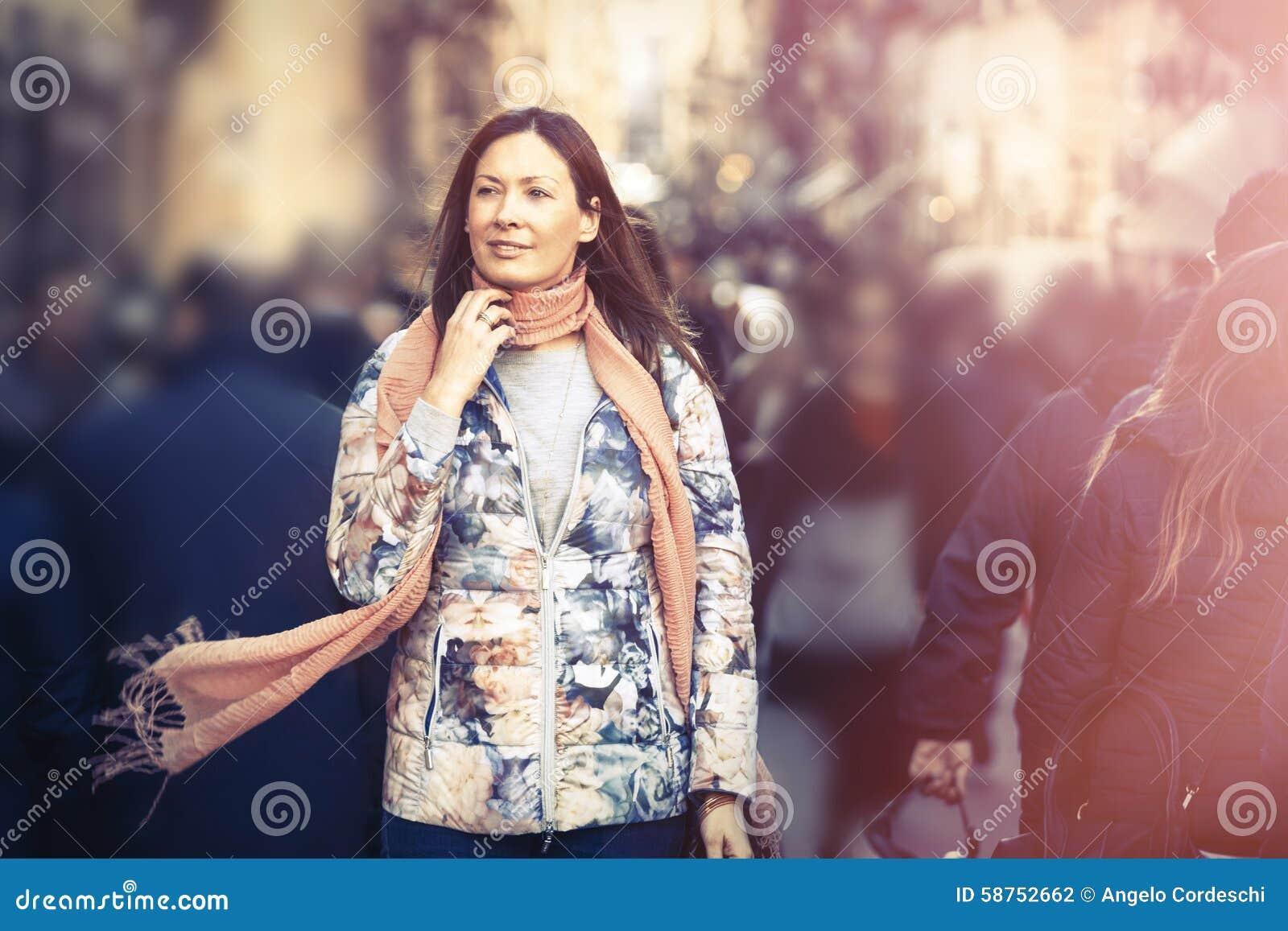 Piękna kobieta z szalika odprowadzeniem w tłumu mieście godziny krajobrazu sezonu zimę