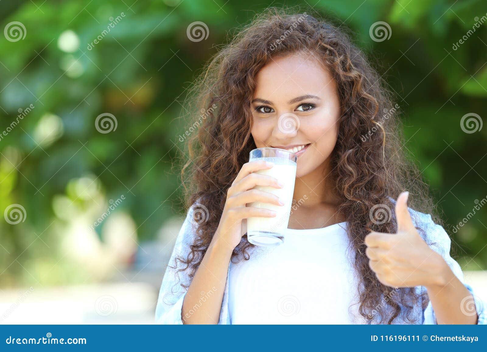 Piękna młoda afroamerykańska kobieta pije mleko