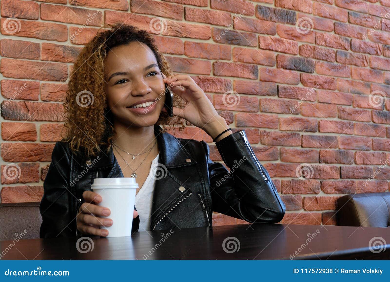 Piękna młoda afroamerykańska kobieta w kurtce z białego papieru szkłem w jeden ręce siedzi przy stołem i ono uśmiecha się, podcza