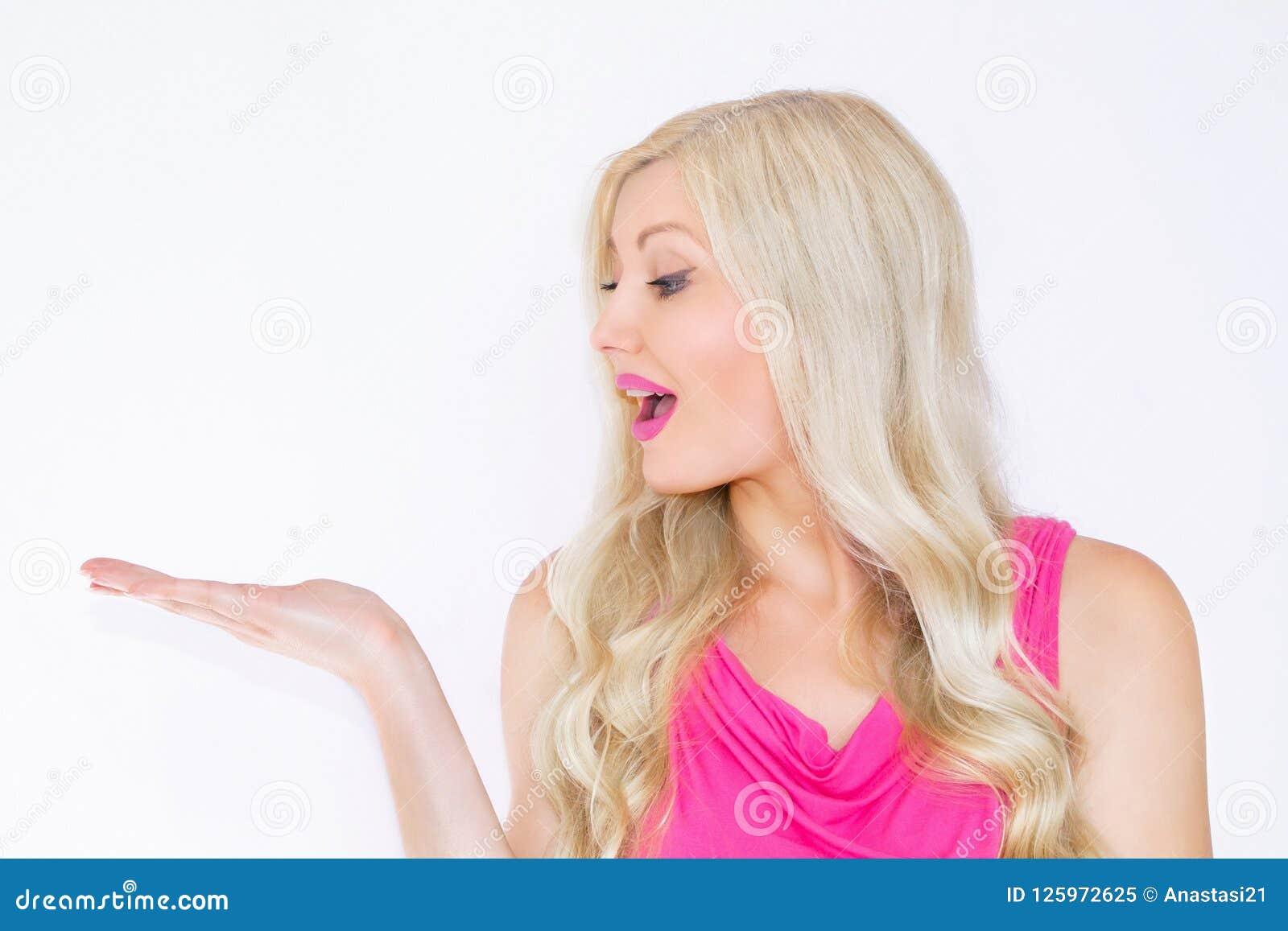 Piękna młoda blond kobieta ono uśmiecha się pokazywać produkt Piękna dziewczyna wskazuje strona Prezentacja twój produkt