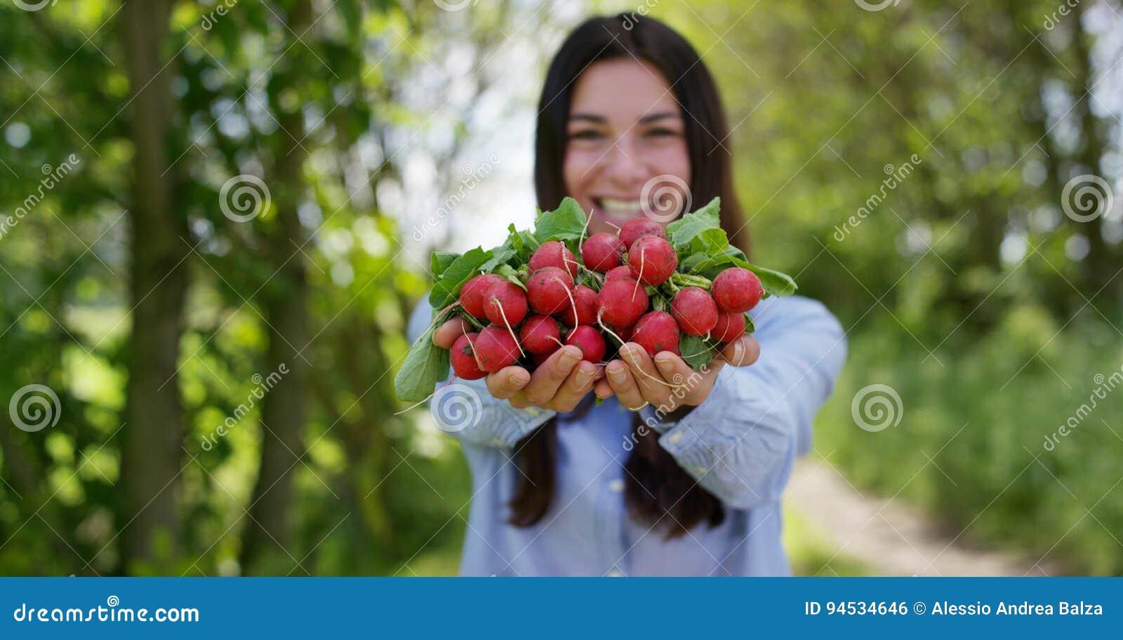 Piękna młoda dziewczyna trzyma czystej rzodkwi w ręce w tle natura, Pojęcie: biologia, życiorys produkty, życiorys ekologia,