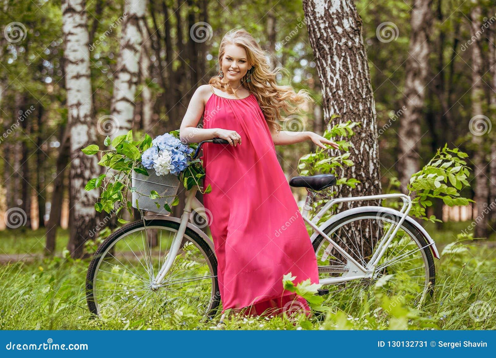 Piękna młoda dziewczyna w lato sukni przy zmierzchem Mody fotografia w lasowym modelu na bicyklu z kwiatu bukietem w menchii l,