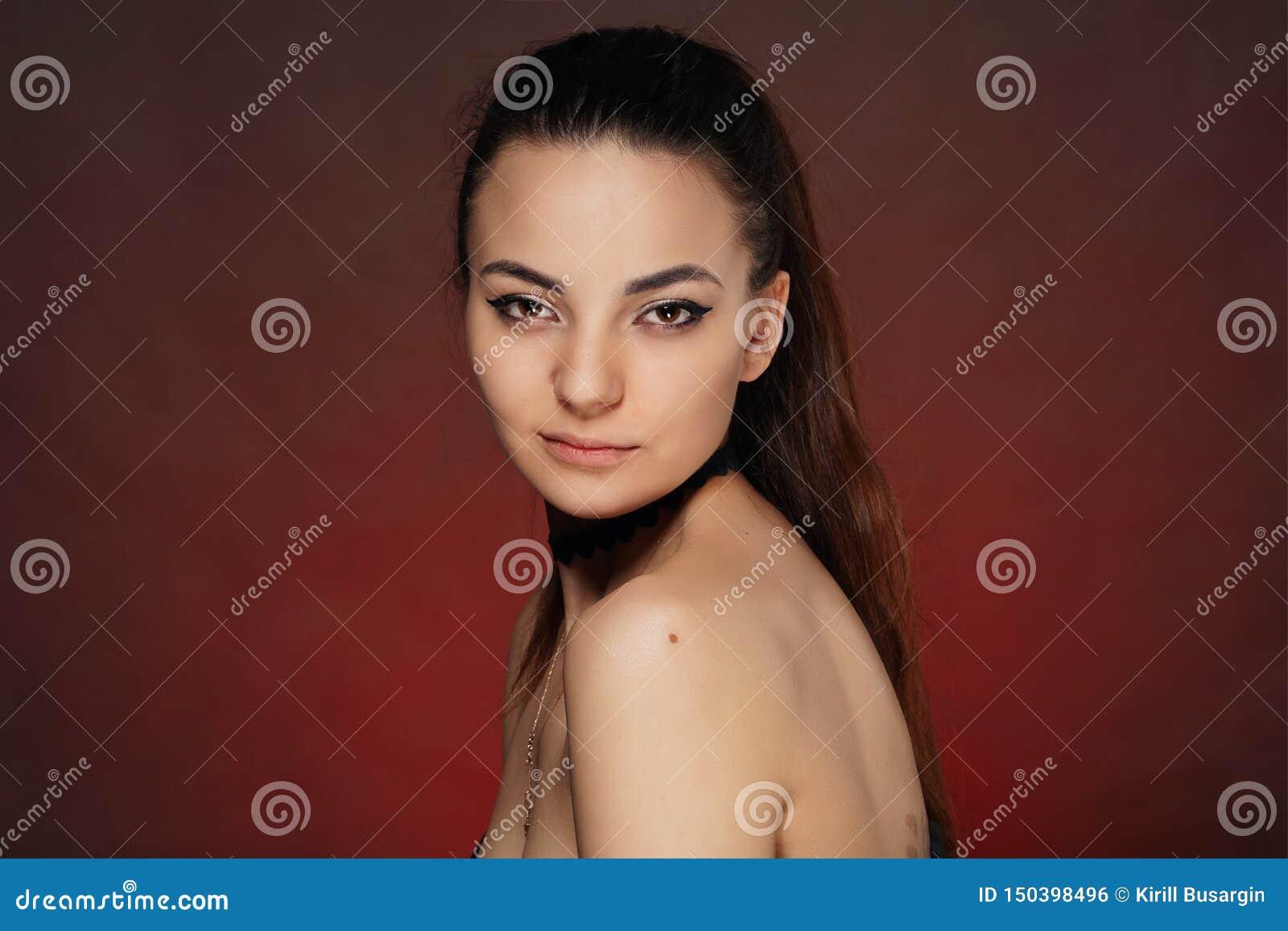 Piękna młoda dziewczyna w studiu na czerwonym tle
