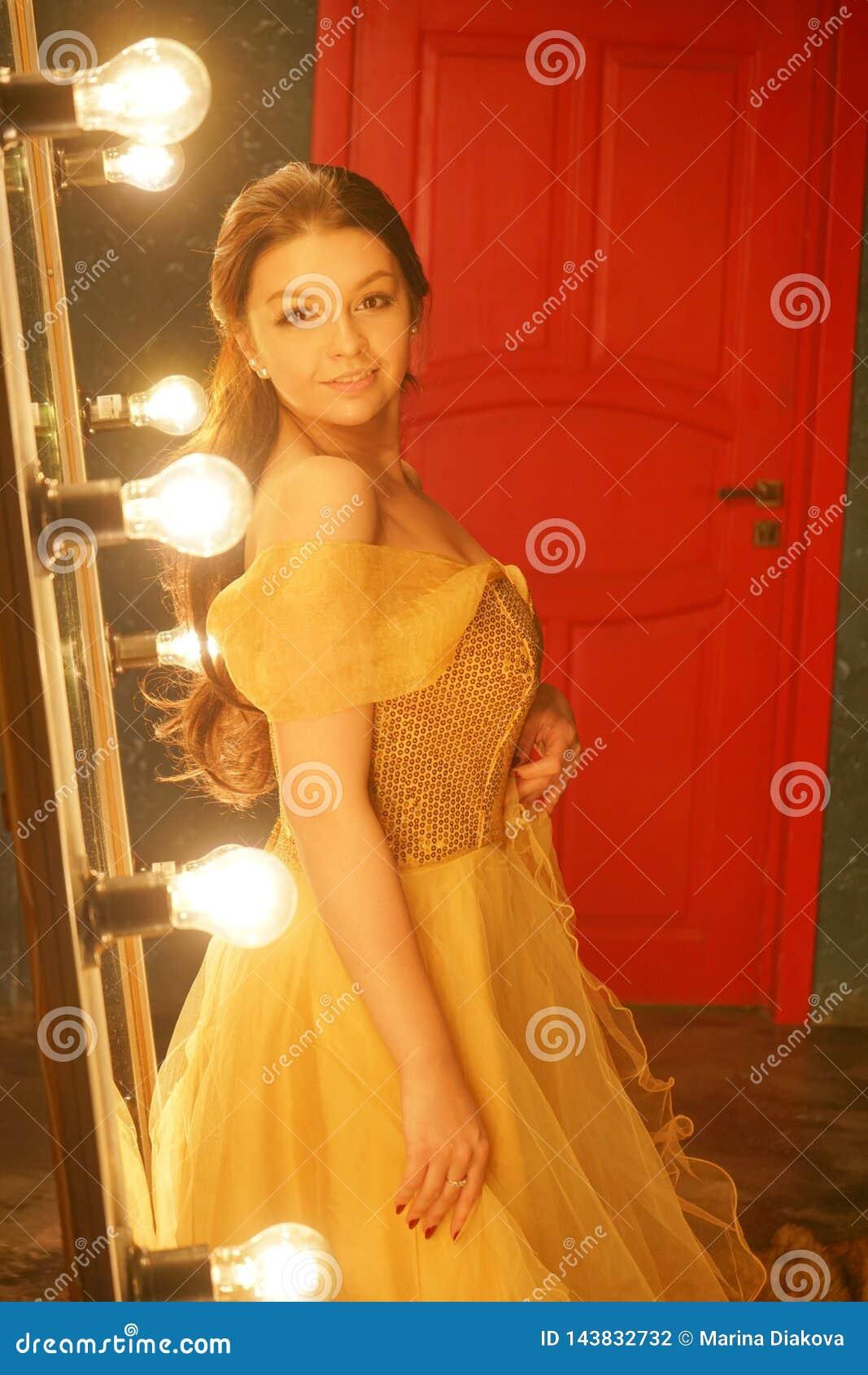 Piękna młoda dziewczyna w wieczór sukni złocistych stojakach na futerkowym dywaniku blisko ampuły lustra w ramie z światłami i sp