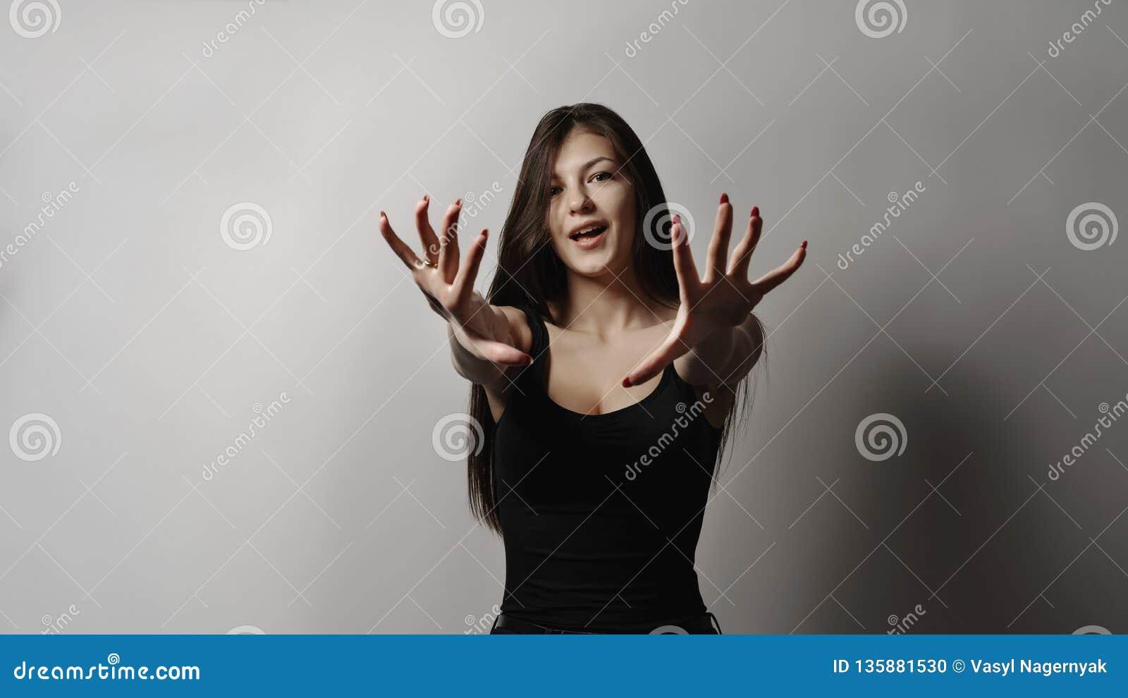 Piękna młoda dziewczyna z czarni włosy na białym tle rozciąga jej ręki naprzód