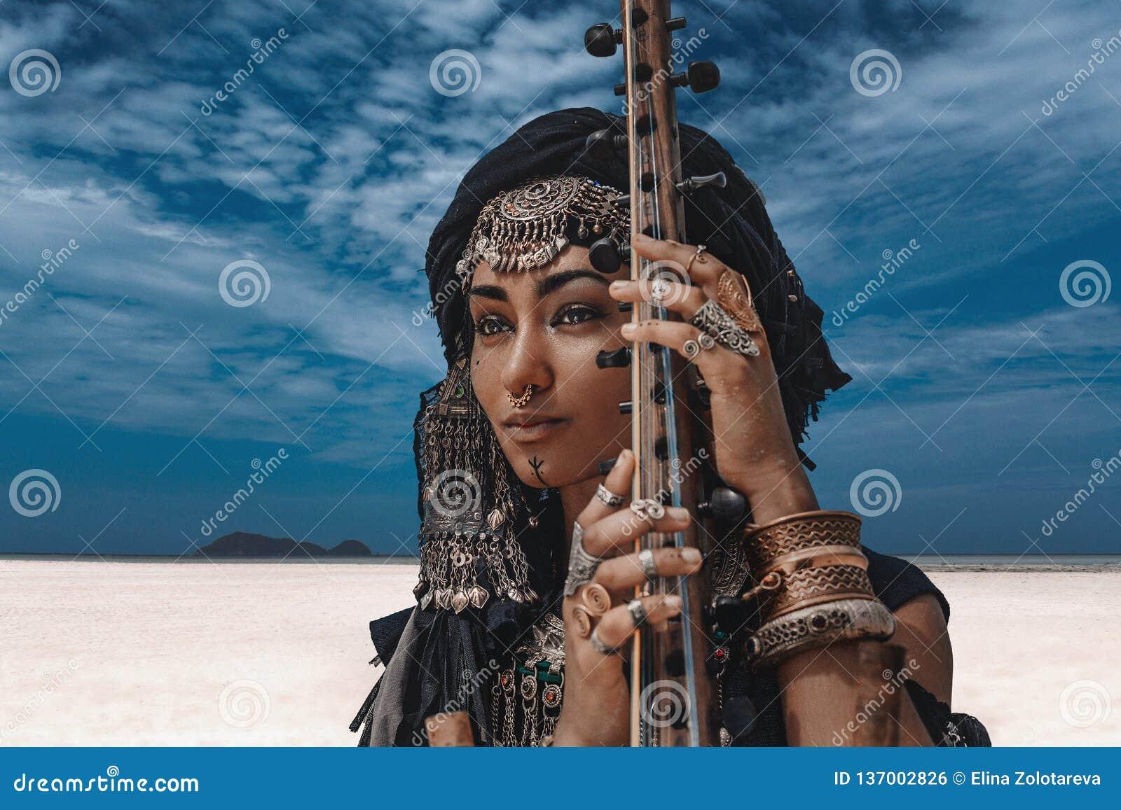 Piękna młoda elegancka plemienna kobieta w orientalnym kostiumowym bawić się sitar outdoors z bliska