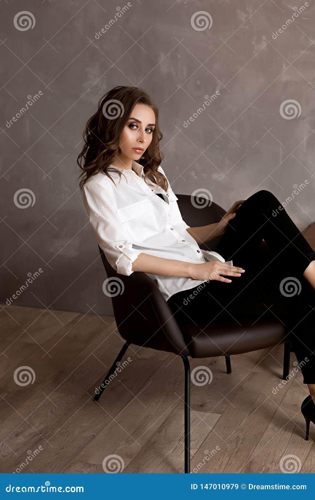 Piękna młoda europejska kobieta w białej koszula i czarnych spodniach siedzi na krześle, dosyć caucasian młoda kobieta z