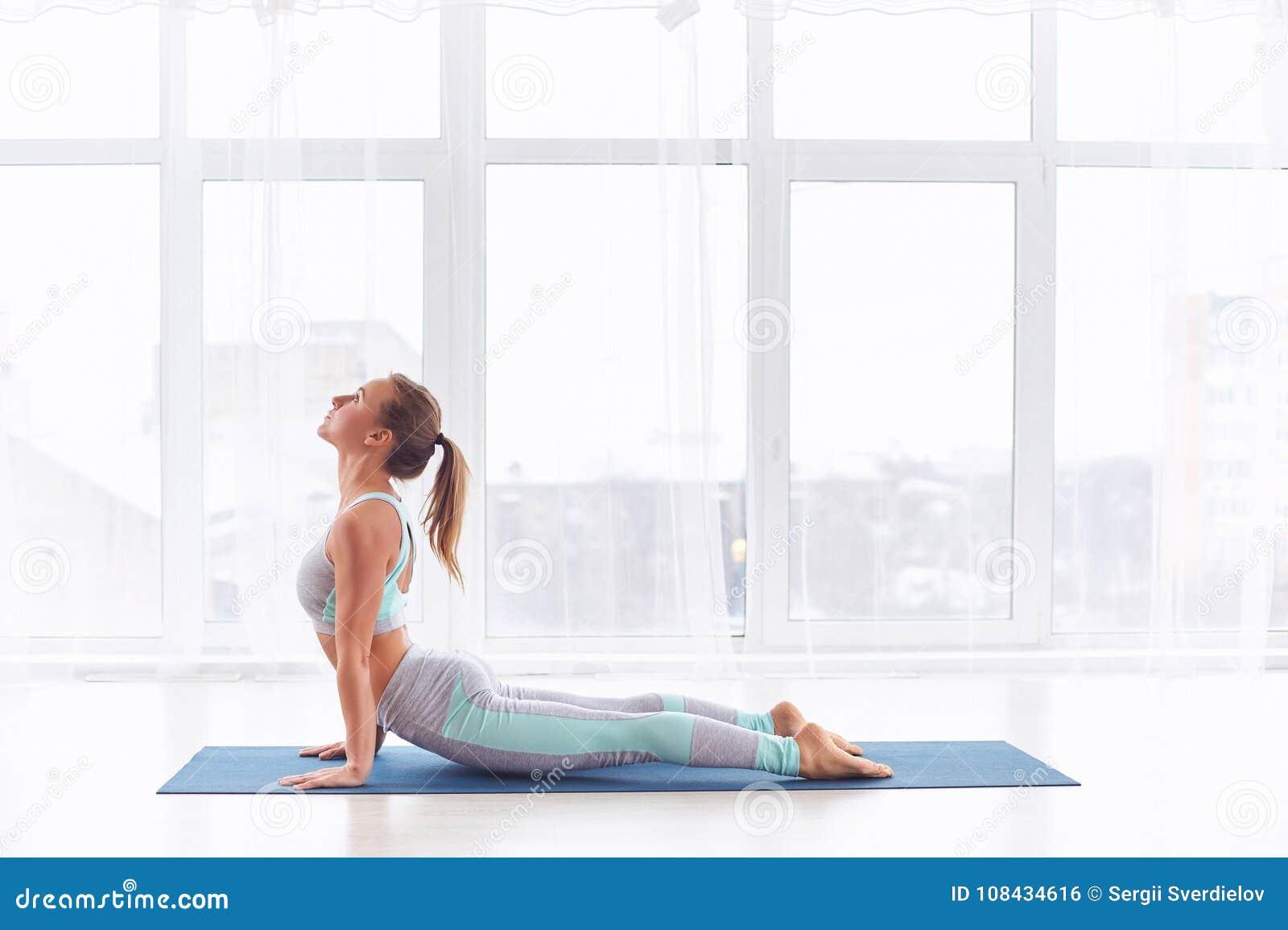 Piękna młoda kobieta ćwiczy joga asana Urdhva Mukha Svanasana - oddolny obszycie pies przy joga klasą