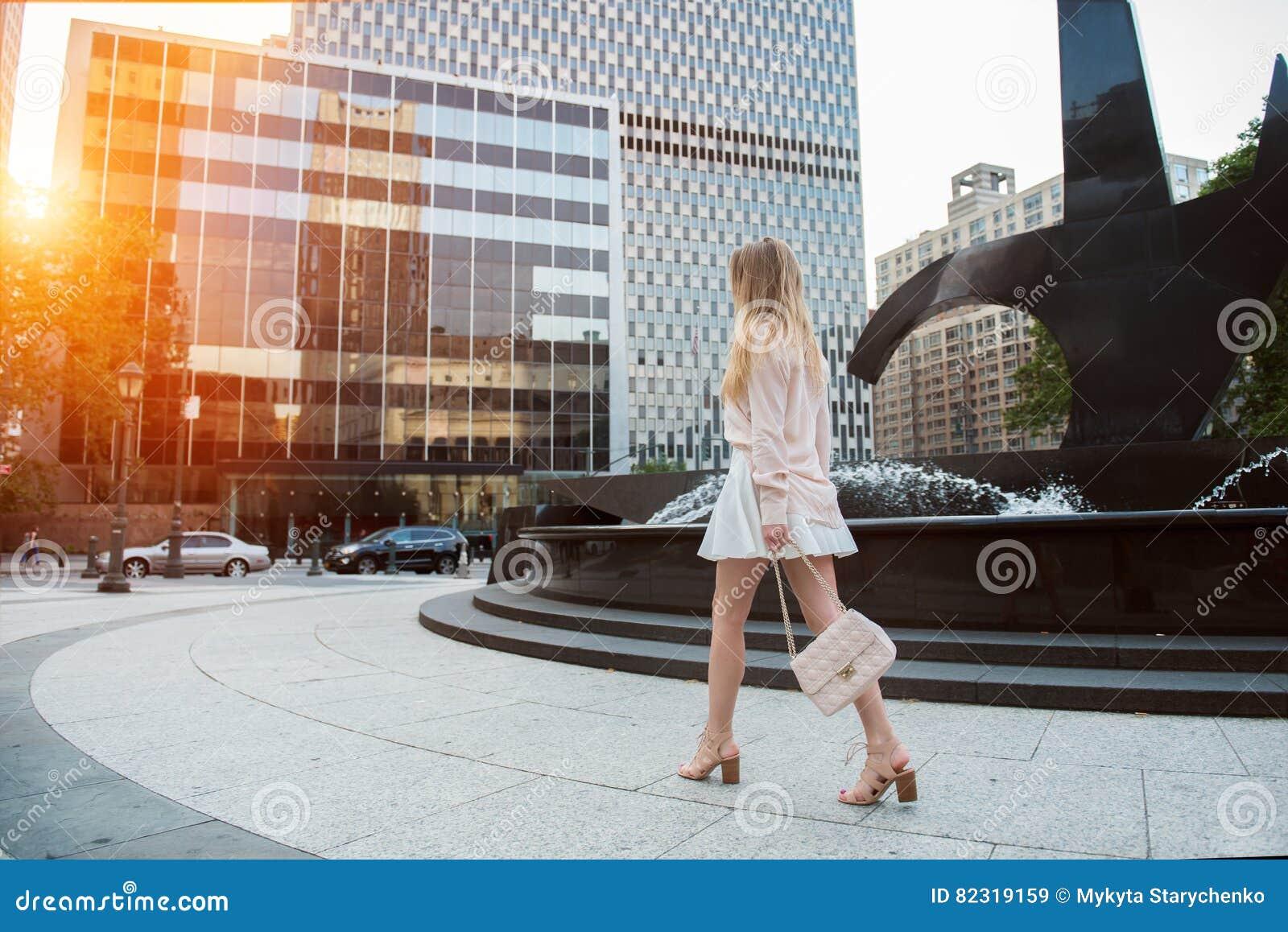 Piękna młoda kobieta chodzi na miasto ulicie jest ubranym i trzyma torbę z długimi nogami krótką spódnicę i menchii koszulkę