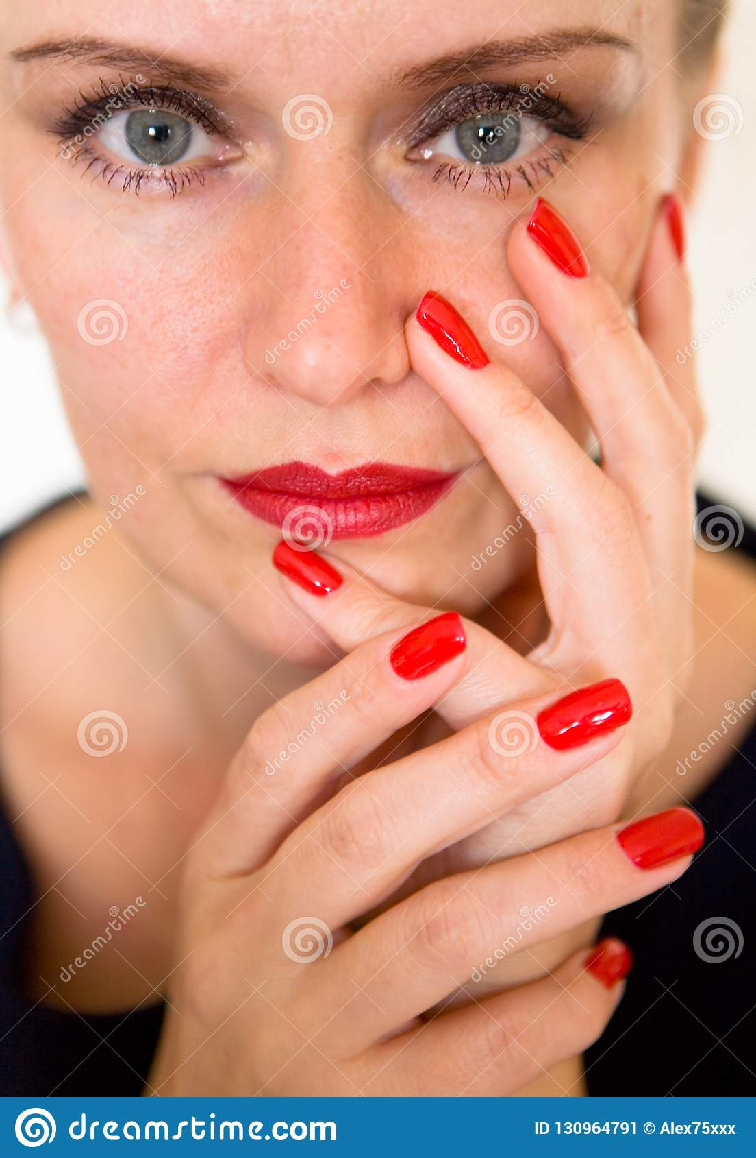 Piękna młoda kobieta dotyka jej twarz z ona palce
