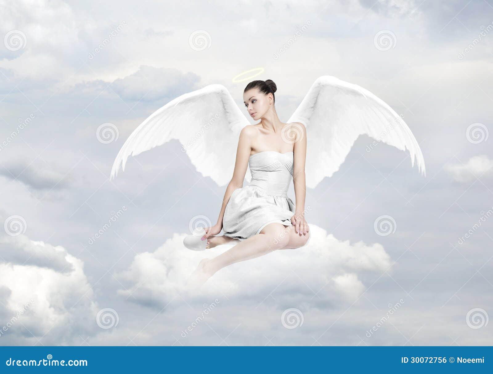 Piękna młoda kobieta jako anioła obsiadanie na chmurze