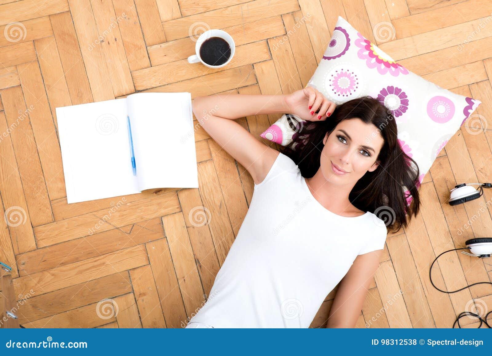 Piękna młoda kobieta kłaść na podłoga z elektronicznym gad,