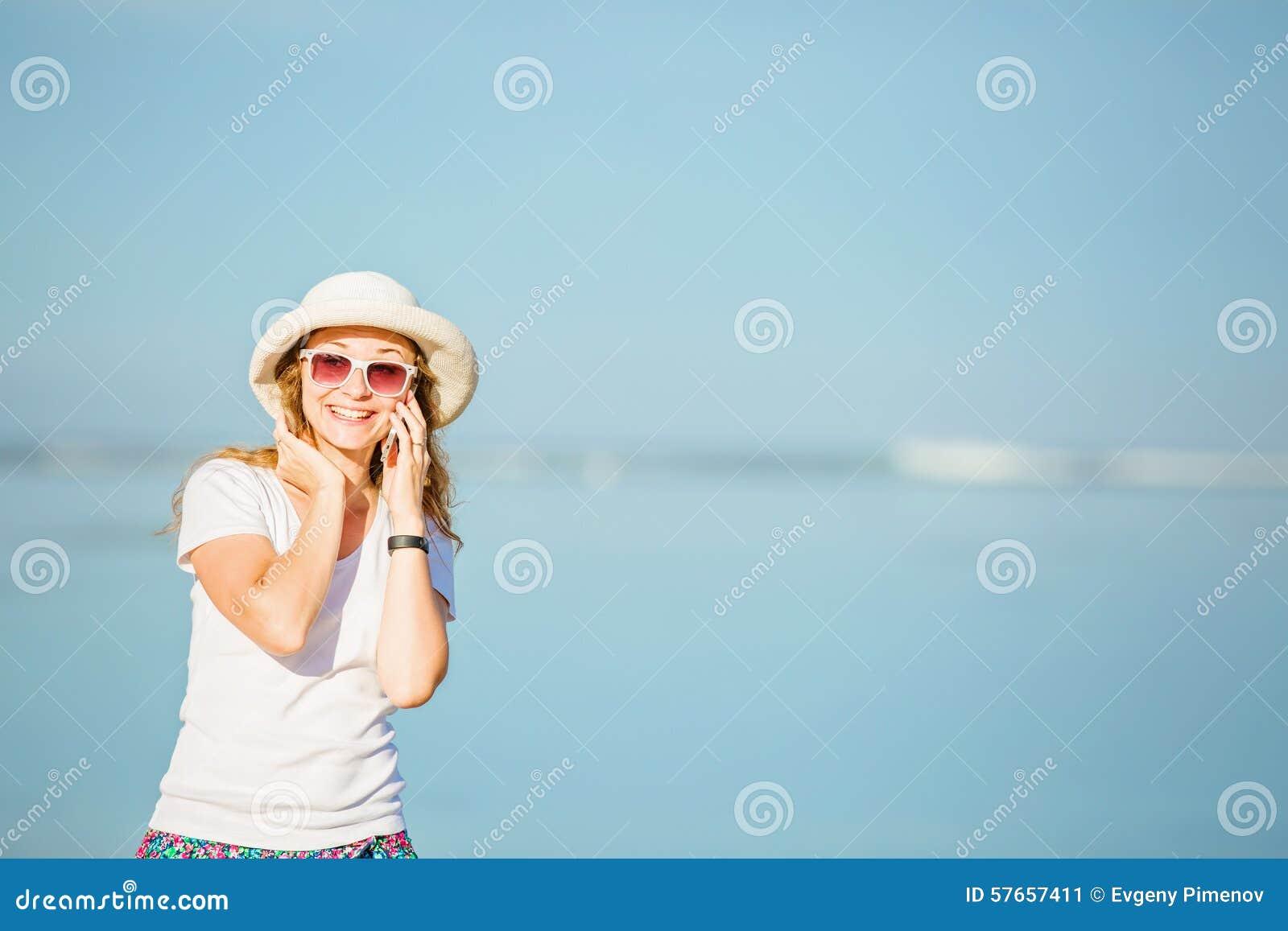 Piękna młoda kobieta opowiada dalej przy plażą