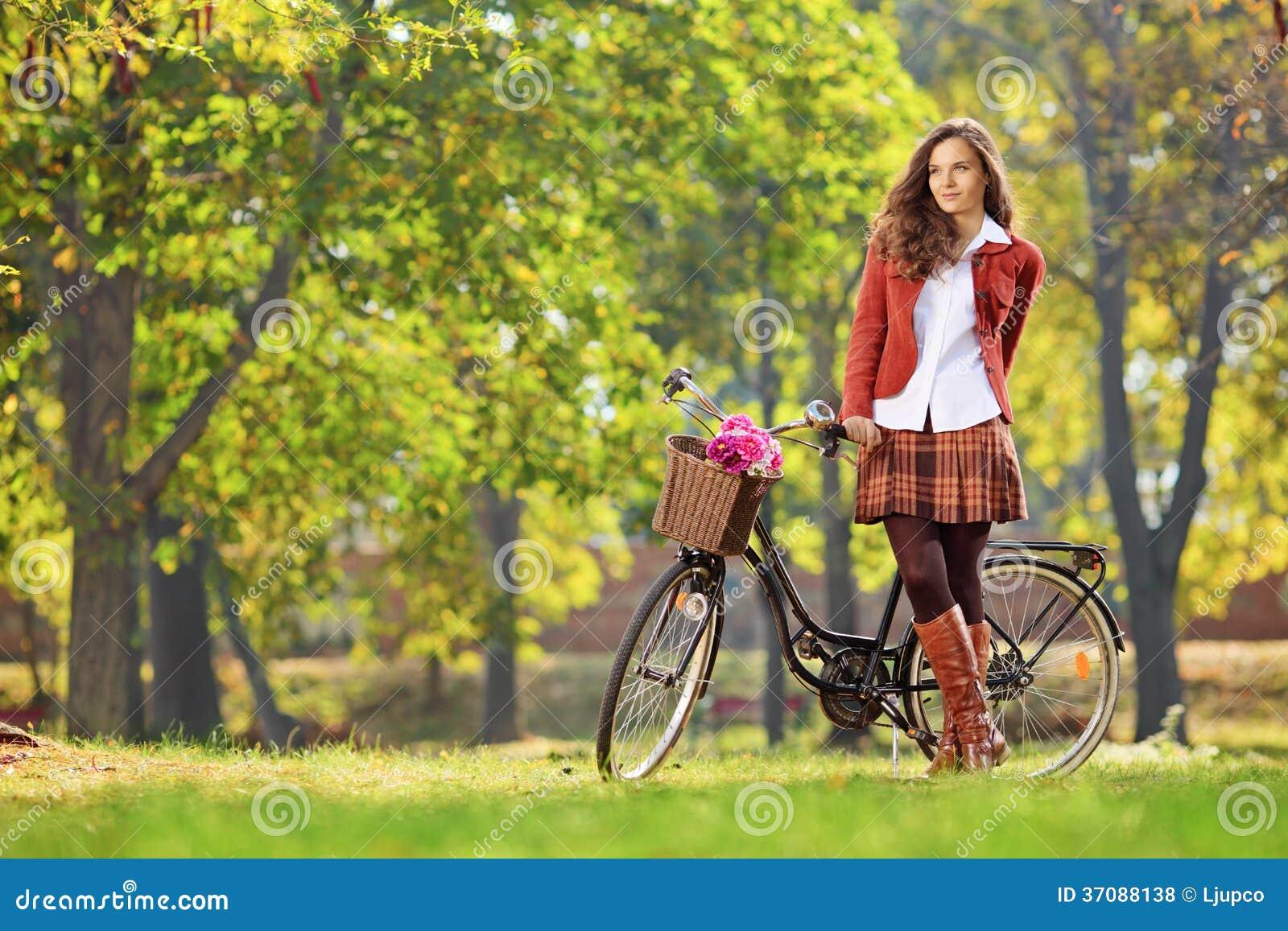 Download Piękna Młoda Kobieta Pozuje W Parku Z Bicyklem Zdjęcie Stock - Obraz złożonej z kwiat, długość: 37088138