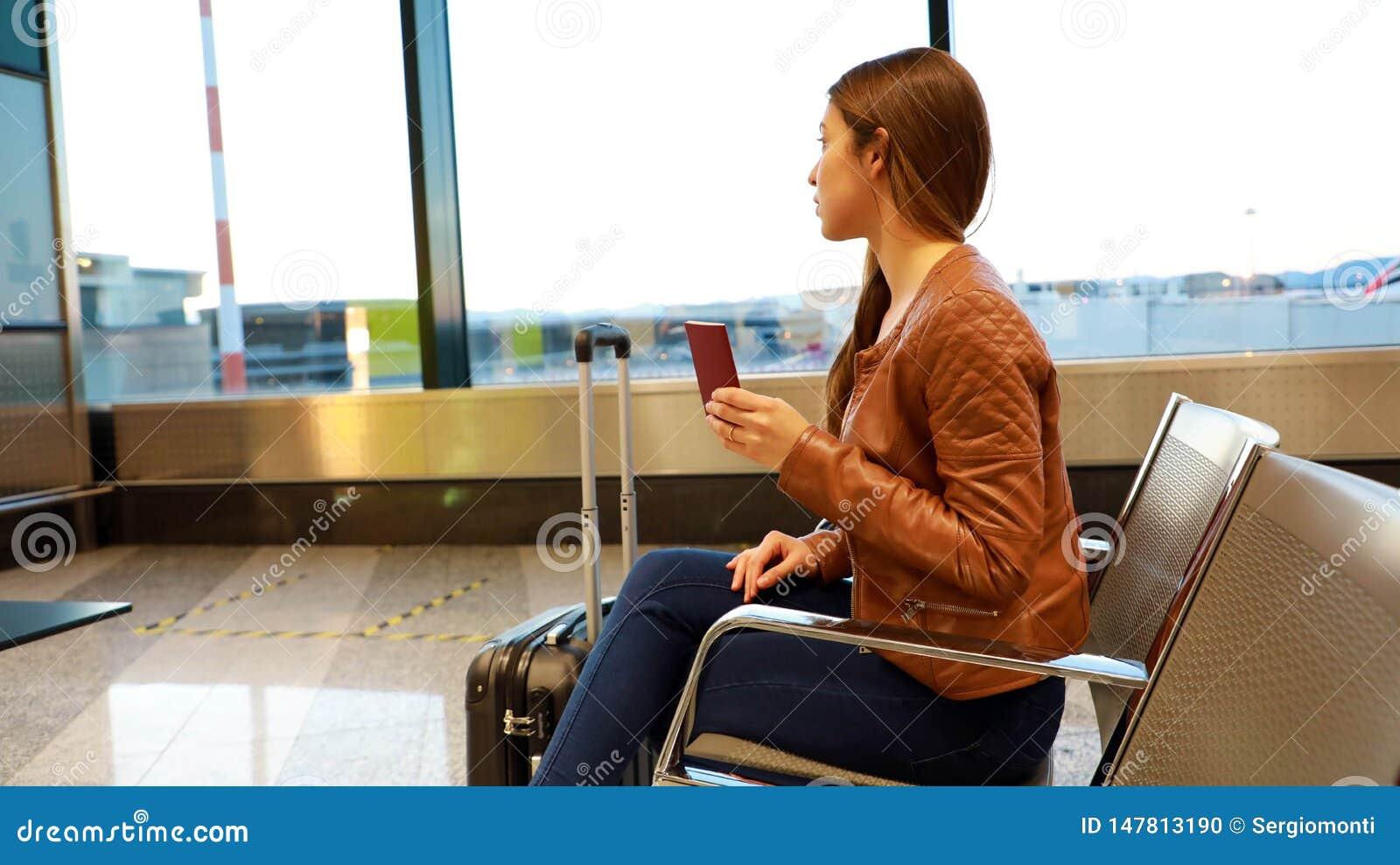 Piękna młoda kobieta przyglądająca za okno podczas gdy czekający wsiadać na samolocie z paszportem w jej ręce