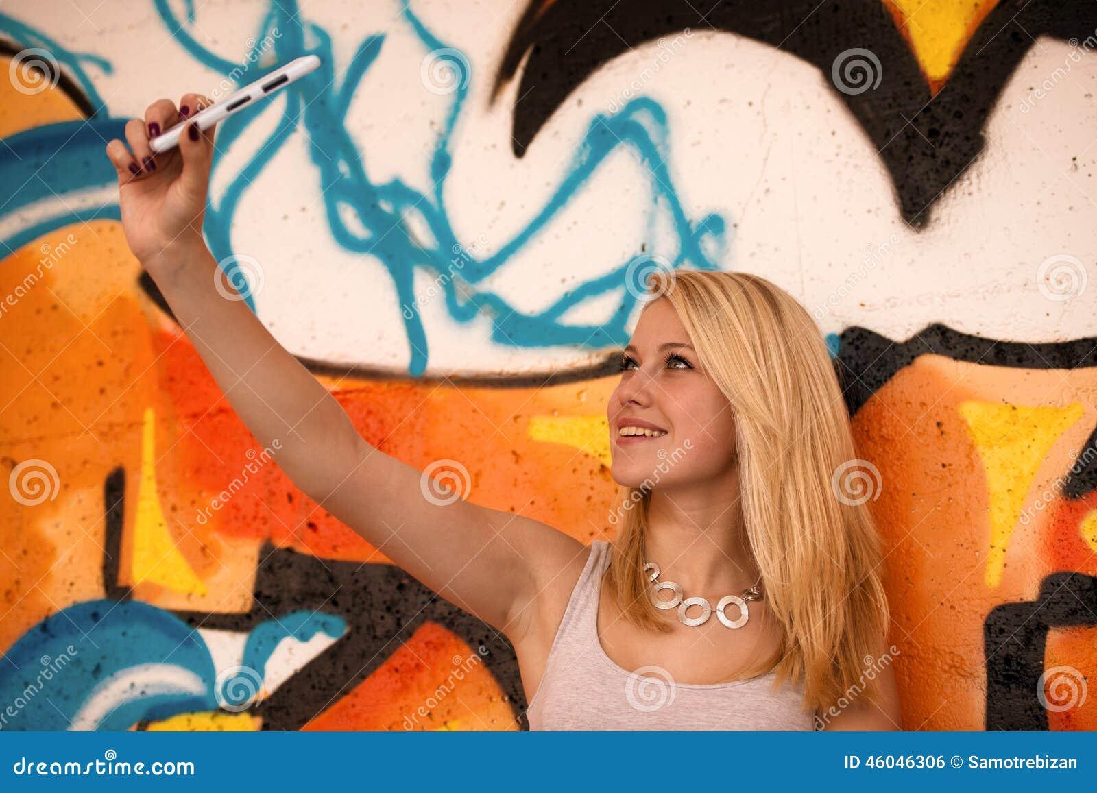 Piękna młoda kobieta robi selfie wal outdoors blisko graffiti