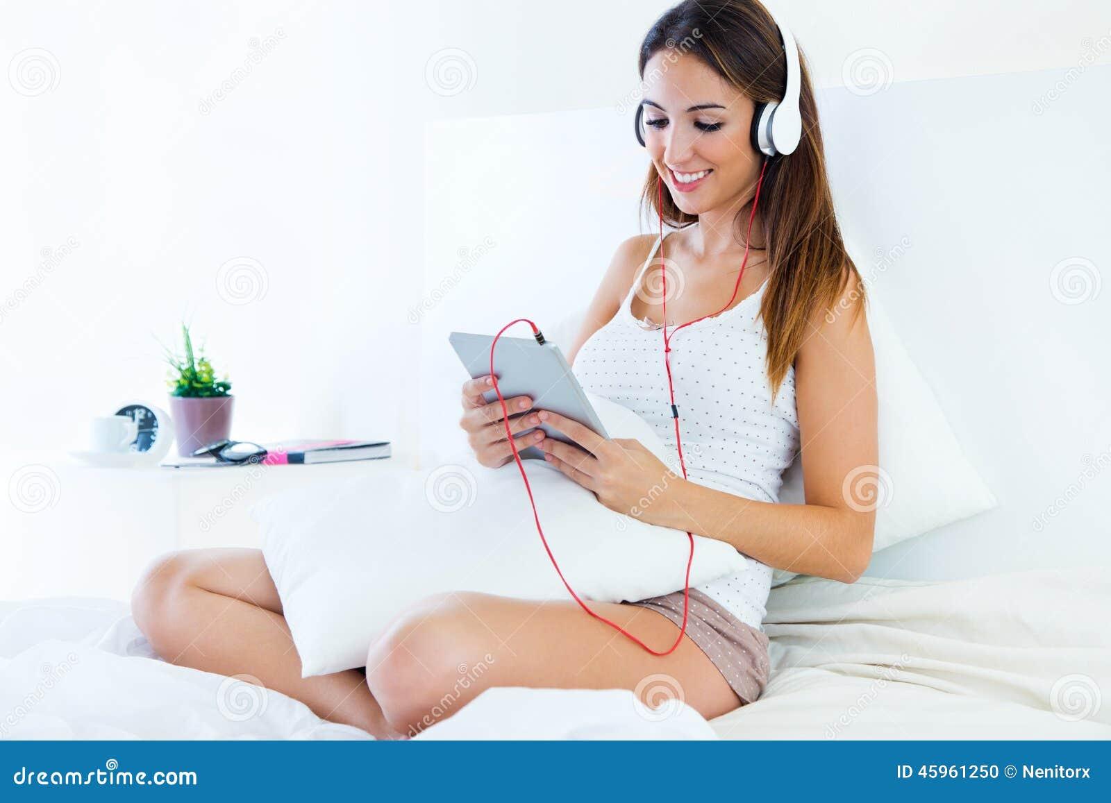 Piękna młoda kobieta słucha muzyka z pastylki obsiadaniem dalej