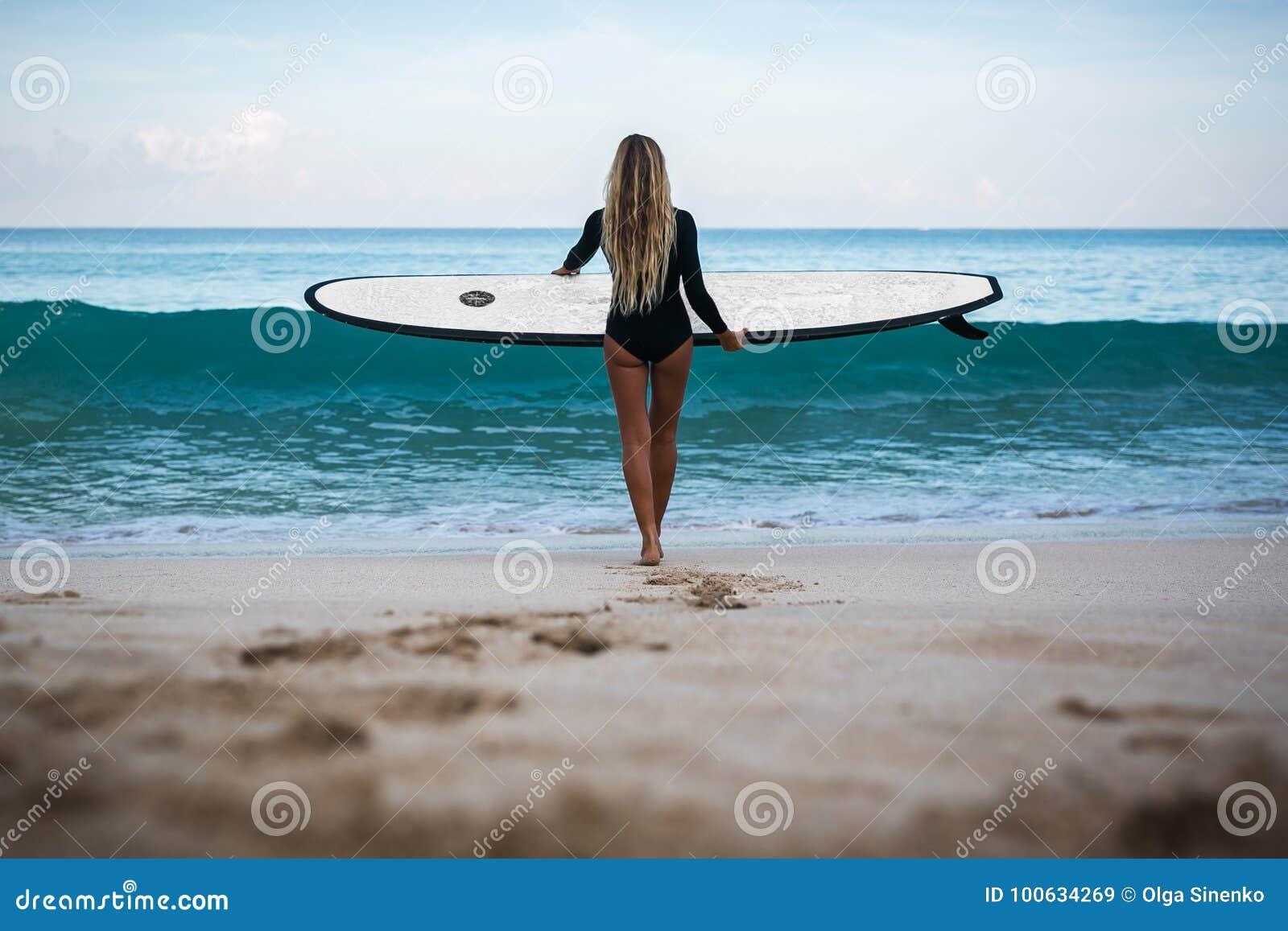 Piękna młoda kobieta w bikini z kipieli deską przy plażą tropikalna wyspa