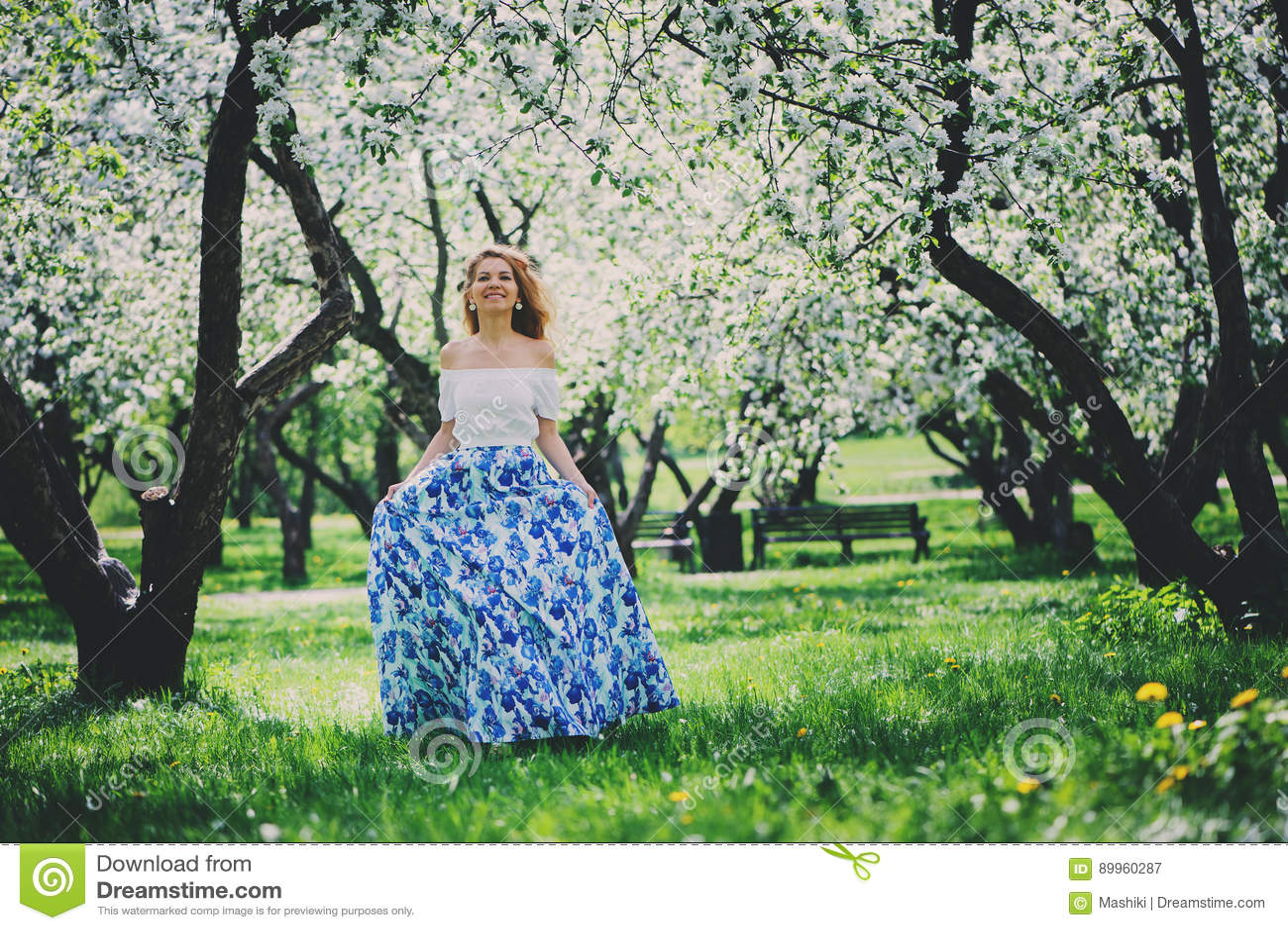 Piękna młoda kobieta w kwiecistym maksim spódnicowym odprowadzeniu w wiośnie