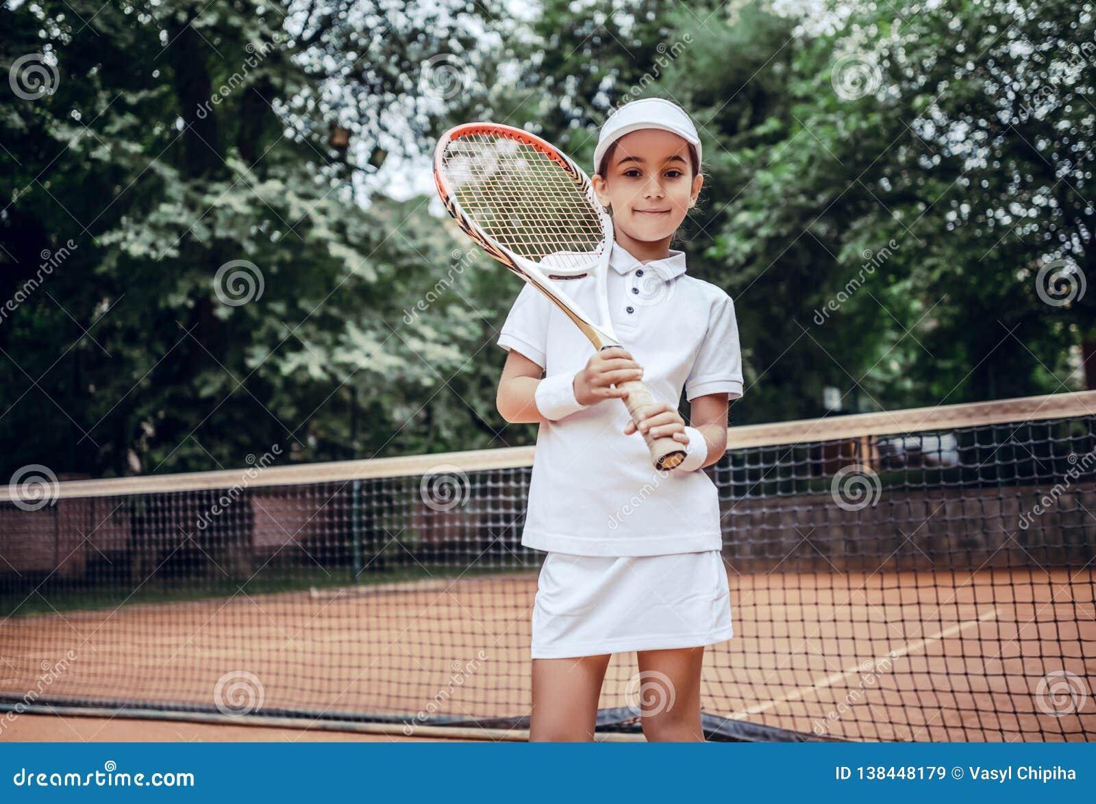 Piękna młoda kobieta w sport odzieży uśmiechniętej i patrzeje daleko od