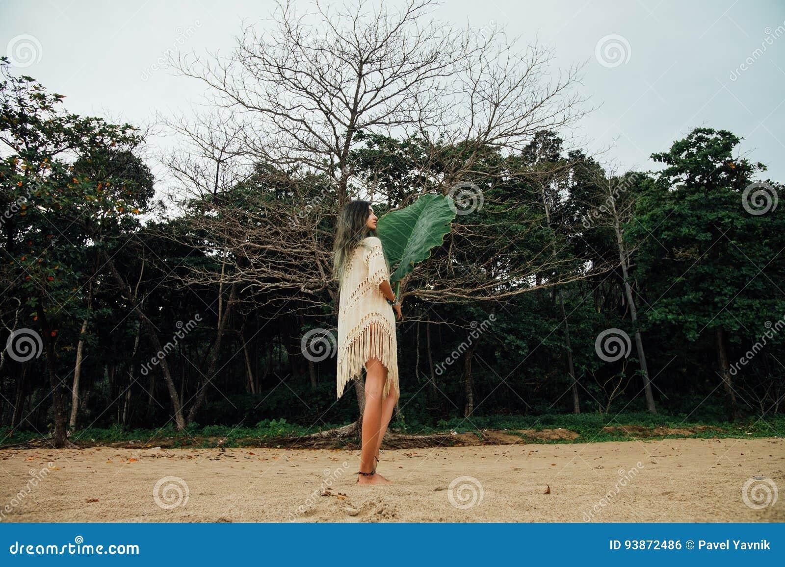 Piękna młoda kobieta w tunice na plaży z wielkiego liścia tropikalnym drzewkiem palmowym
