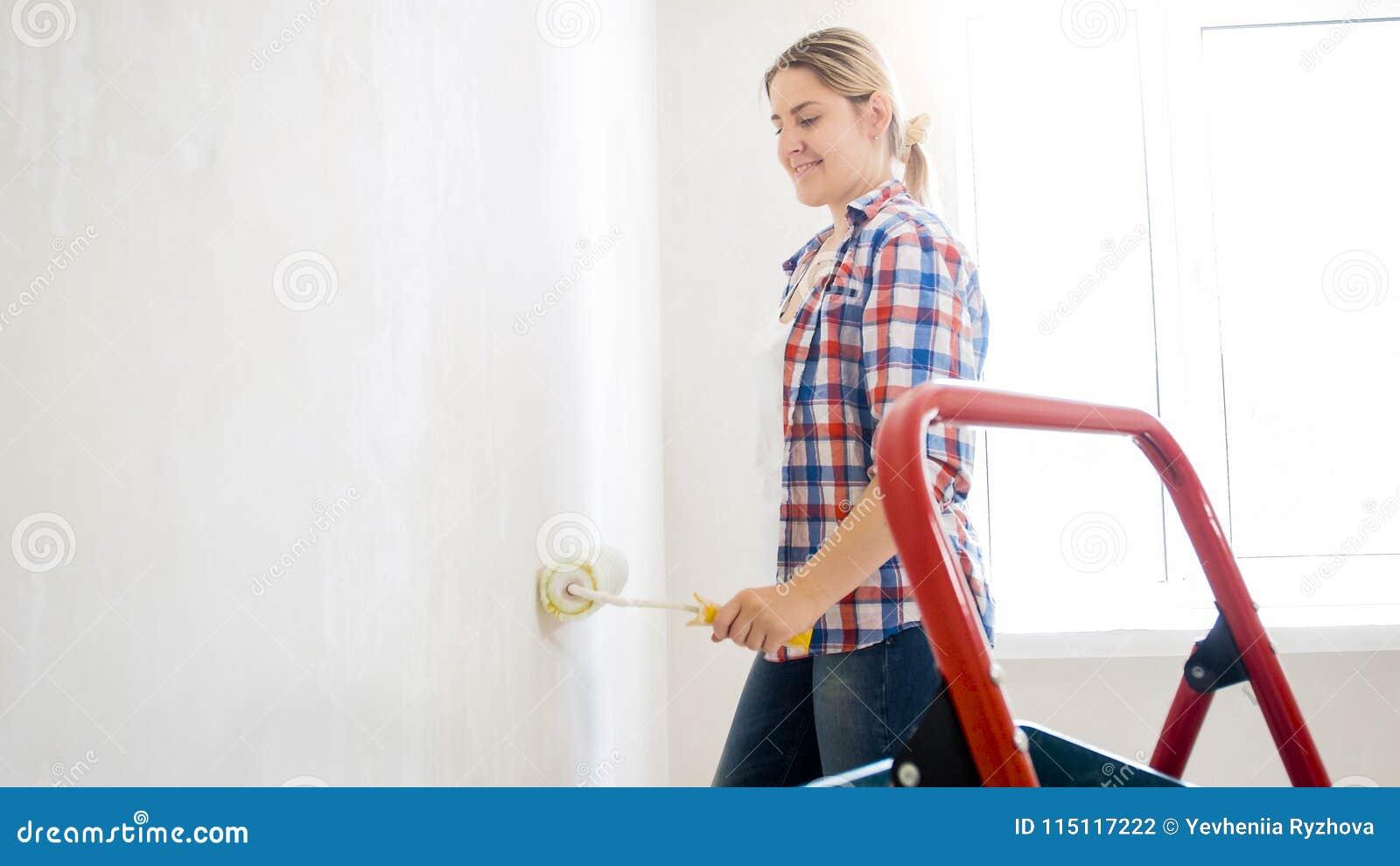 Piękna młoda kobieta z farba rolownikiem robi odświeżaniu przy nowym domem