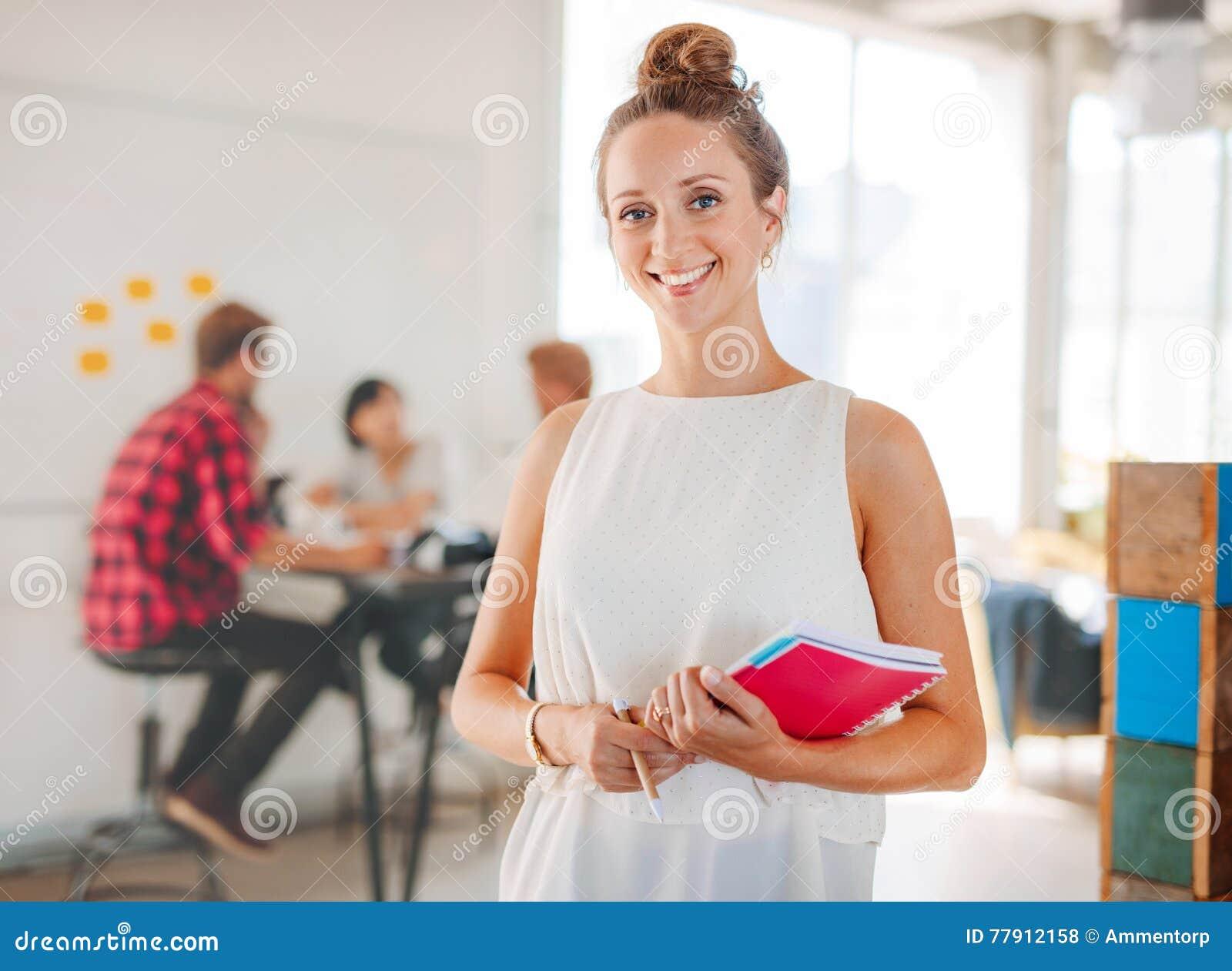 Piękna młoda kobieta z kolegami spotyka w tle