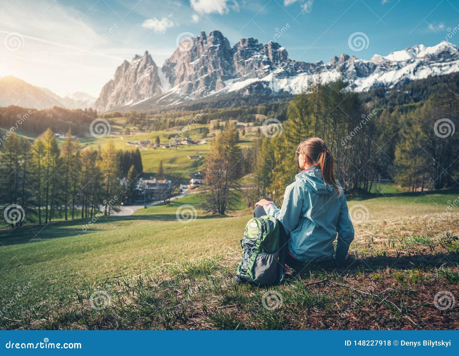 Piękna młoda kobieta z plecakiem siedzi na wzgórzu