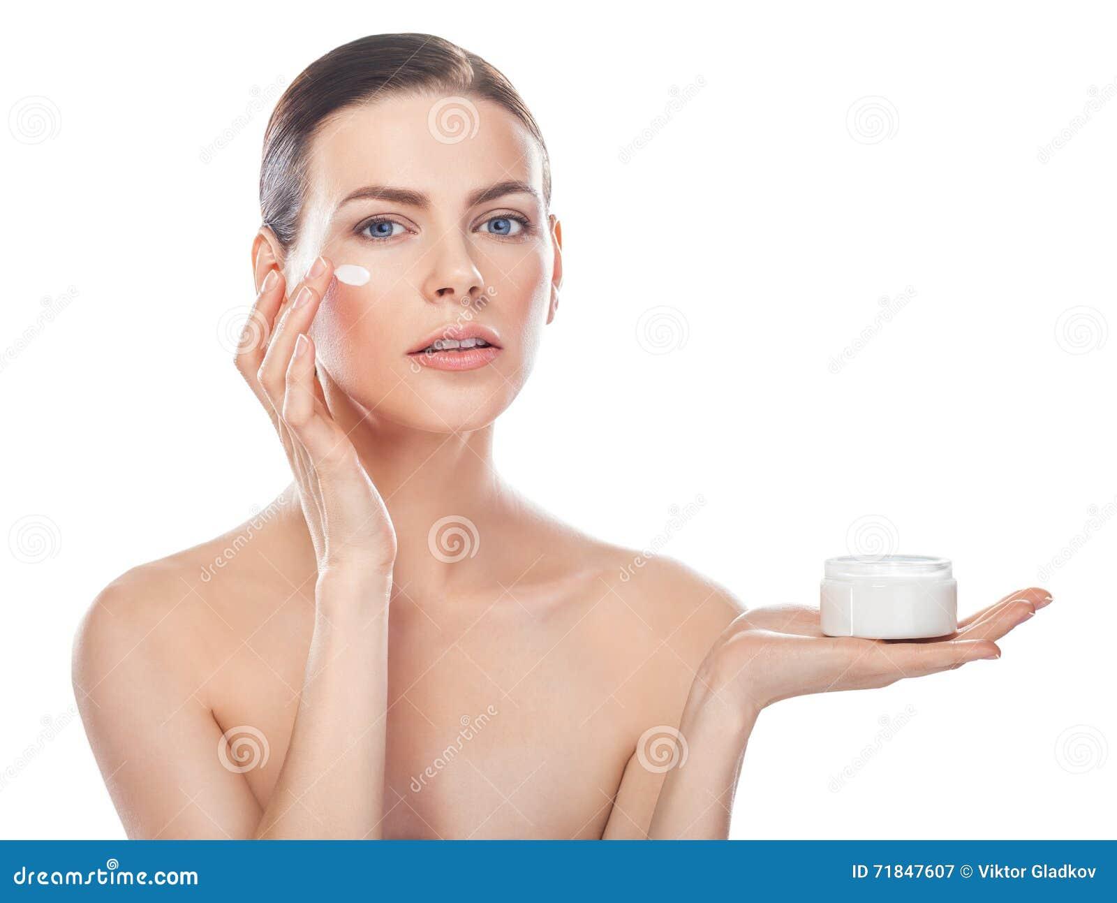 Piękna młoda kobieta z słojem kremowa i kosmetyczna śmietanka na a