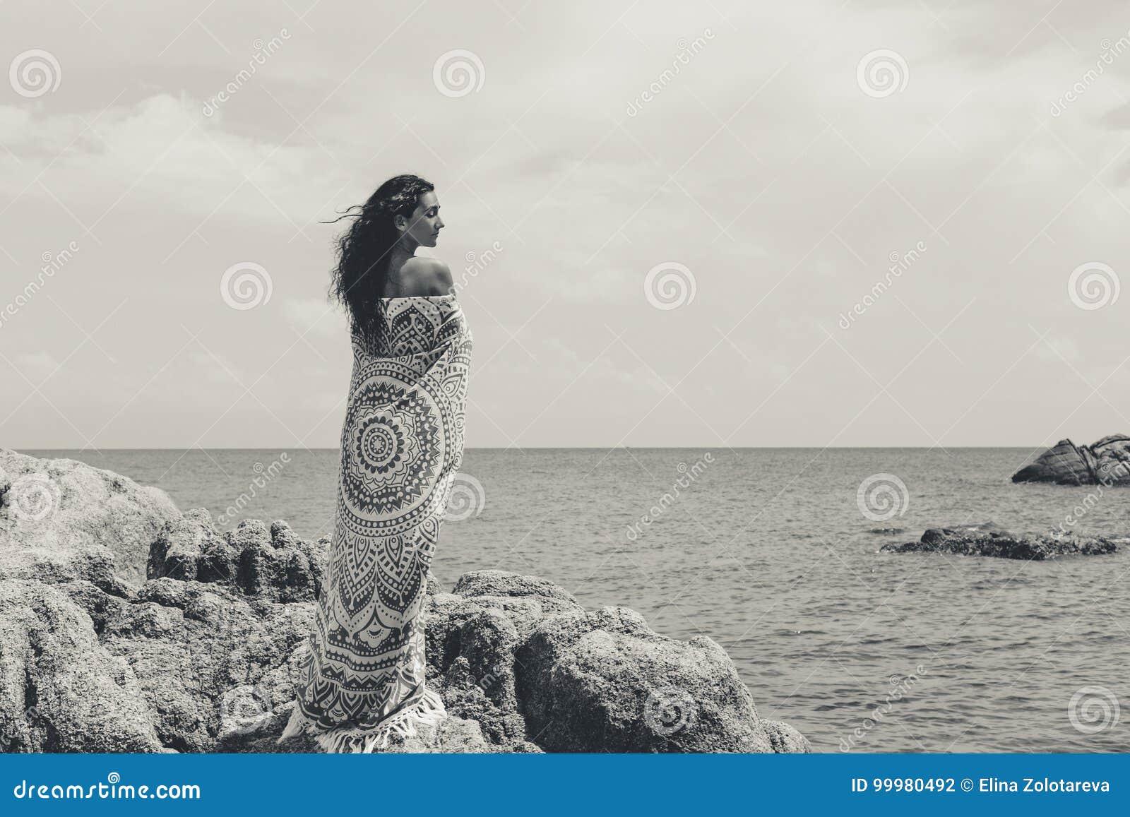 Piękna młoda kobieta zakrywająca z koc na z plażą