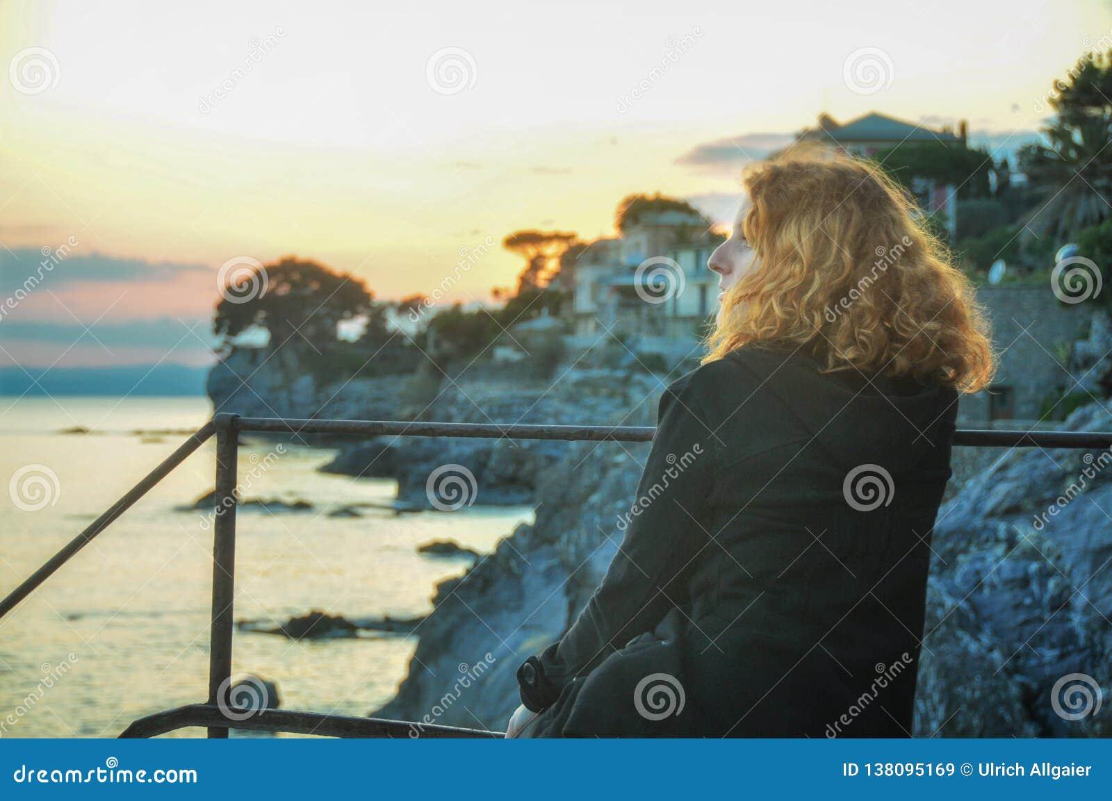 Piękna młoda miedzianowłosa kobieta przy nadmorski w wiosce rybackiej w Liguria, Włochy cieszy się zmierzch