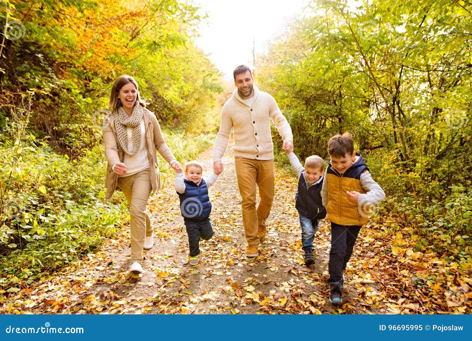 Piękna młoda rodzina na spacerze w jesień lesie