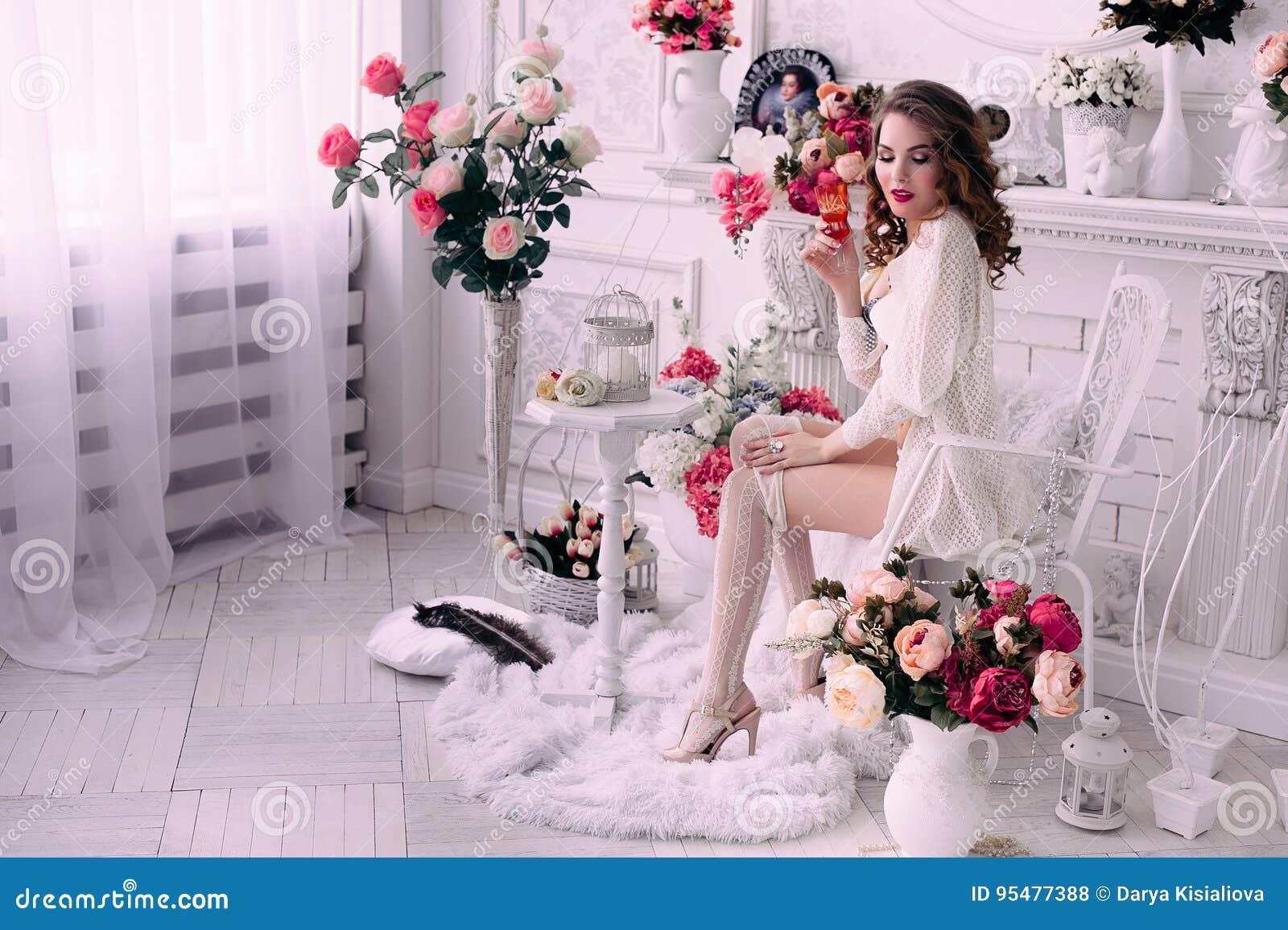 Piękna młoda seksowna kobieta, trzymający obsiadanie w krześle i szkło, jest ubranym białą bieliznę, pokój dekorował z kwiatami _