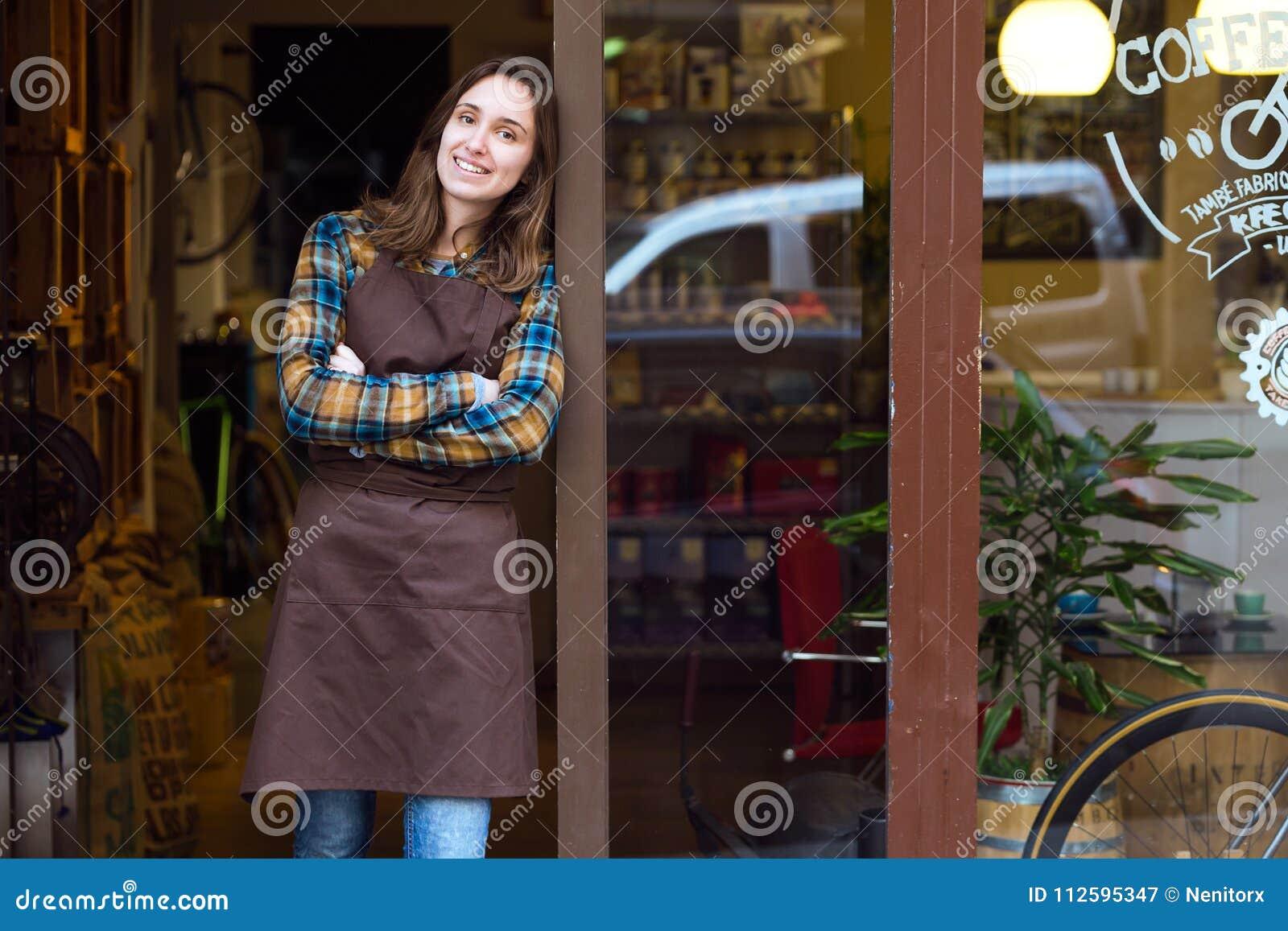 Piękna młoda sprzedawczyni patrzeje kamerę i opiera przeciw drzwiowej ramie organicznie sklep