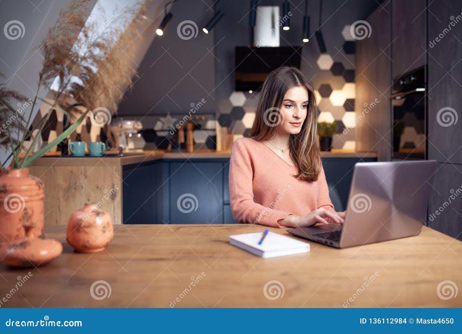 Piękna młoda uśmiechnięta kobieta pracuje od domu