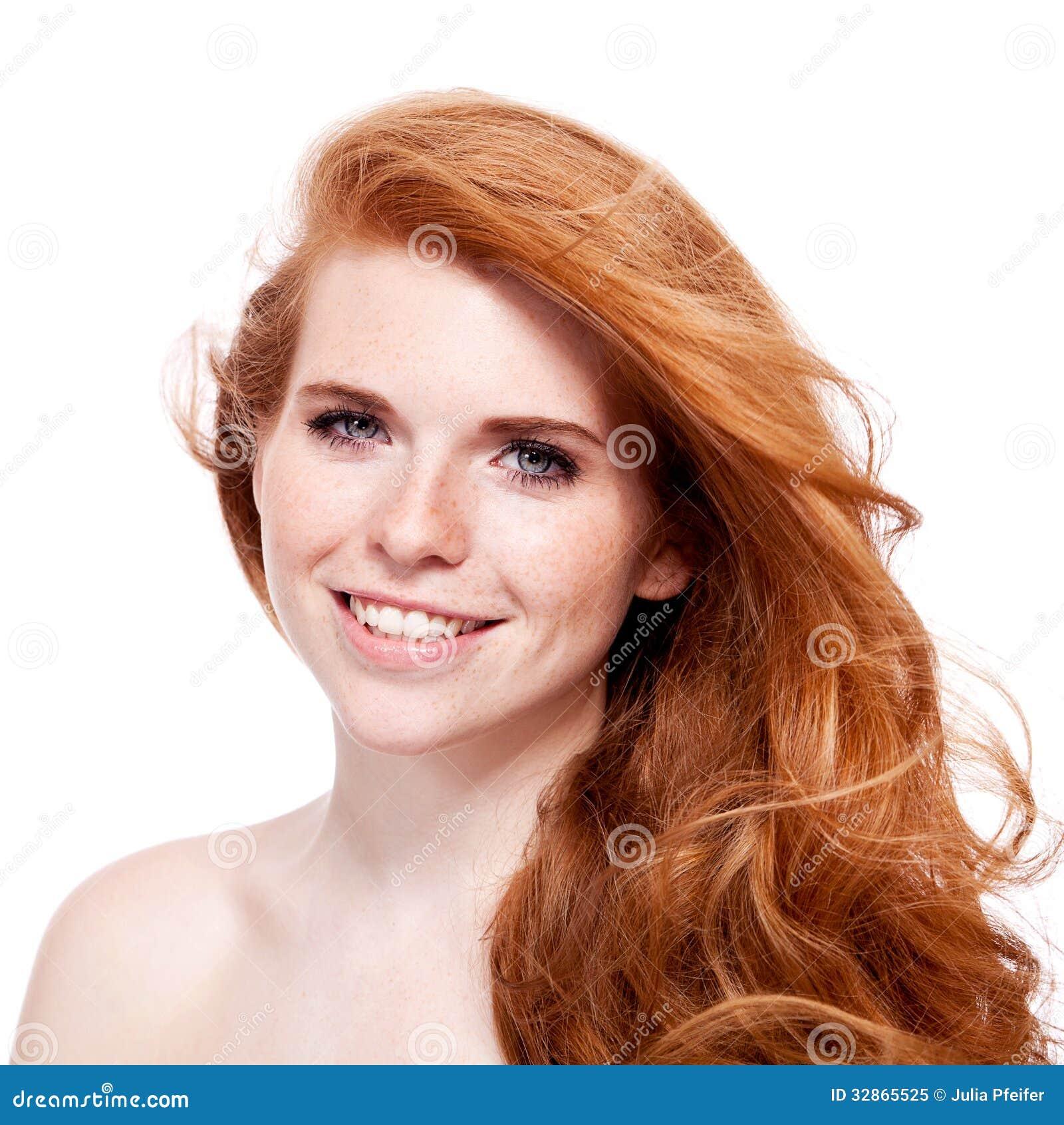 Piękna młoda uśmiechnięta kobieta z czerwonym włosy i piegami odizolowywającymi