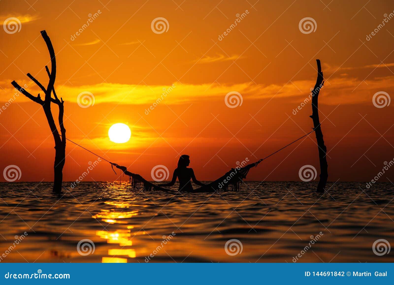 Piękna młodej kobiety sylwetka z huśtawką pozuje w morzu na zmierzchu, maldivian romantyczna sceneria