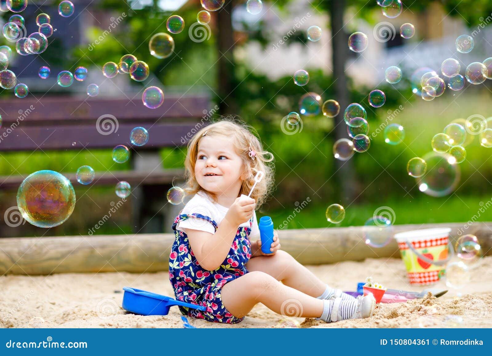 Piękna mała blondynka berbecia dziewczyna ma zabawę z dmuchać mydlanego bąbla dmuchawę Śliczny uroczy dziecka dziecko bawić się d