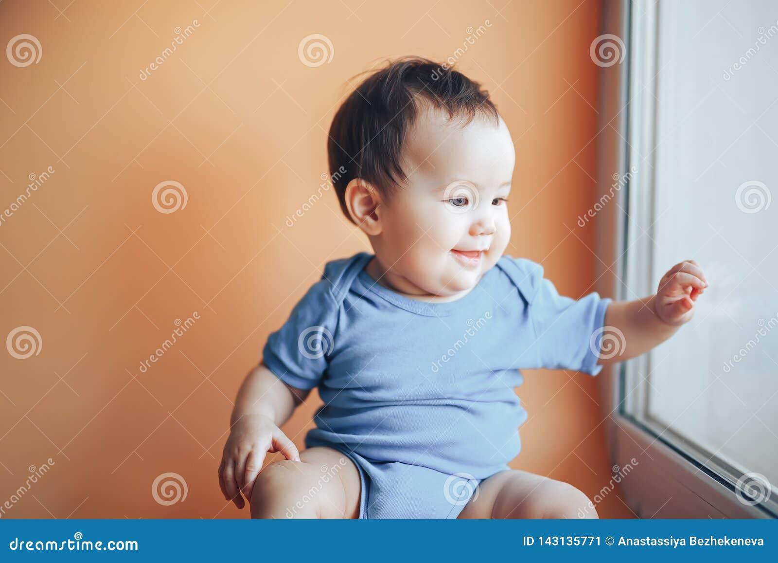 Piękna mała dziewczyna lub chłopiec z ciemnym włosy ono uśmiecha się na jaskrawym pomarańczowym tła colour 2019 z przestrzenią dl