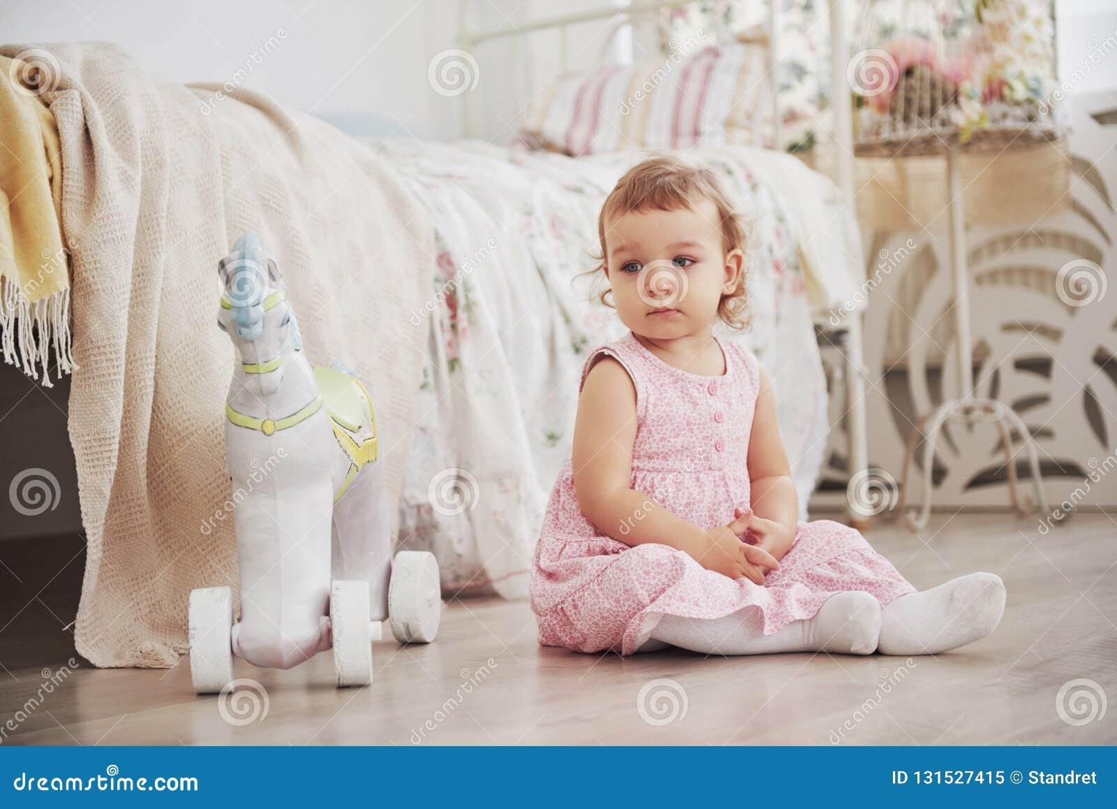 Piękna mała dziewczynka bawić się zabawki niebieski się blondynki Biały krzesło Dziecka ` s pokój Szczęśliwy mały dziewczyna port